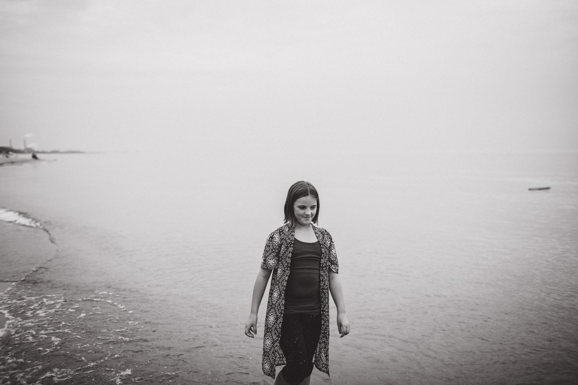 a girl calmly walking along the beach