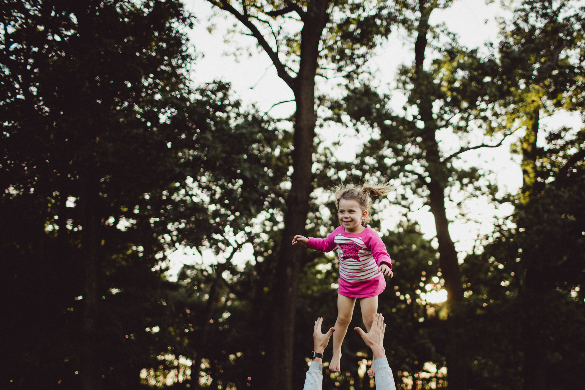 girl being thrown in the air in joy by her father