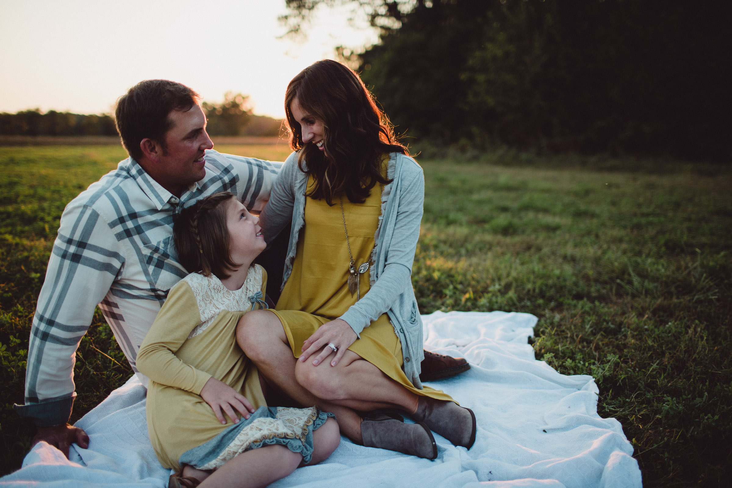parents seated and loving on their daughter