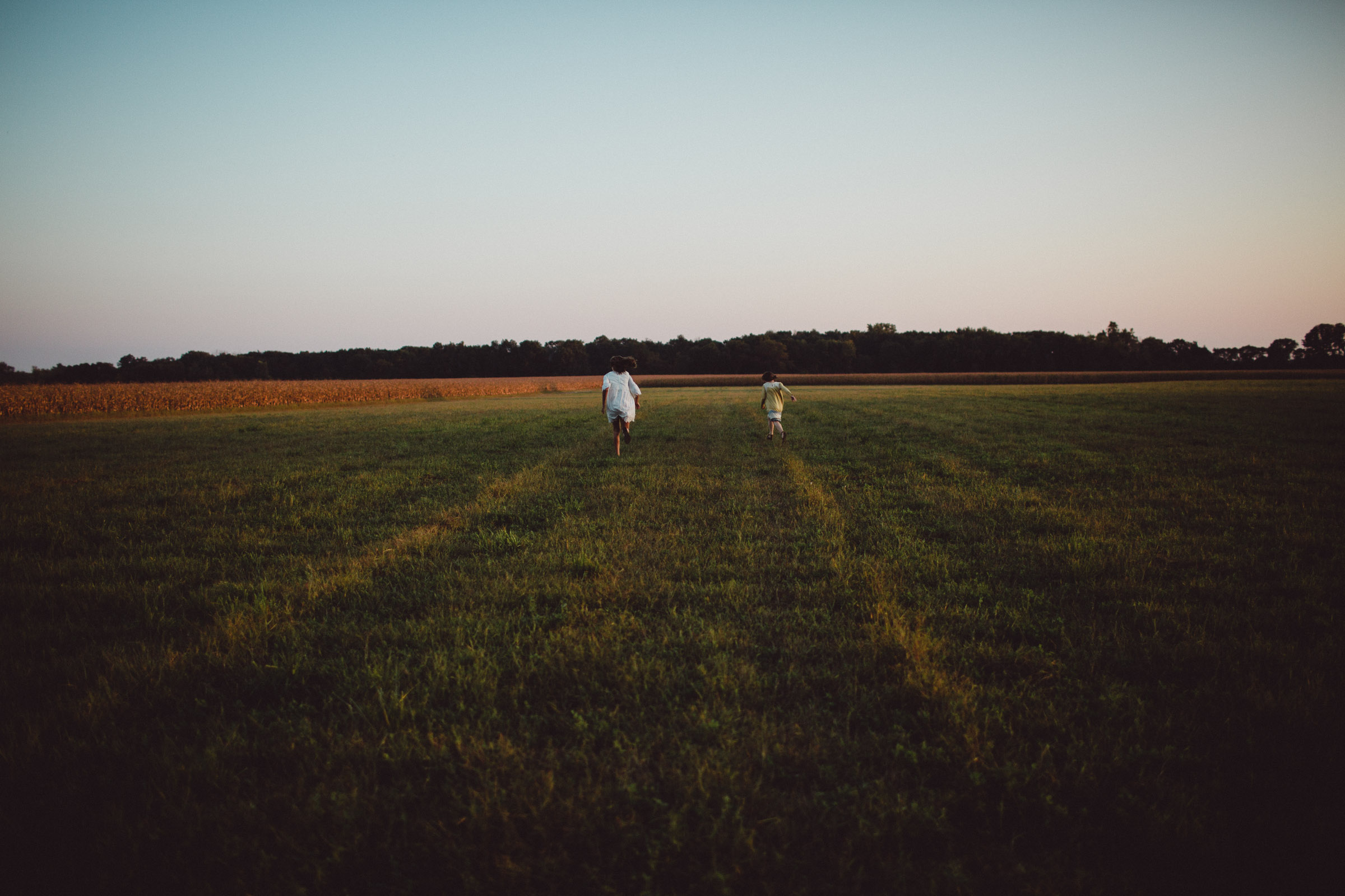sisters running freely through field