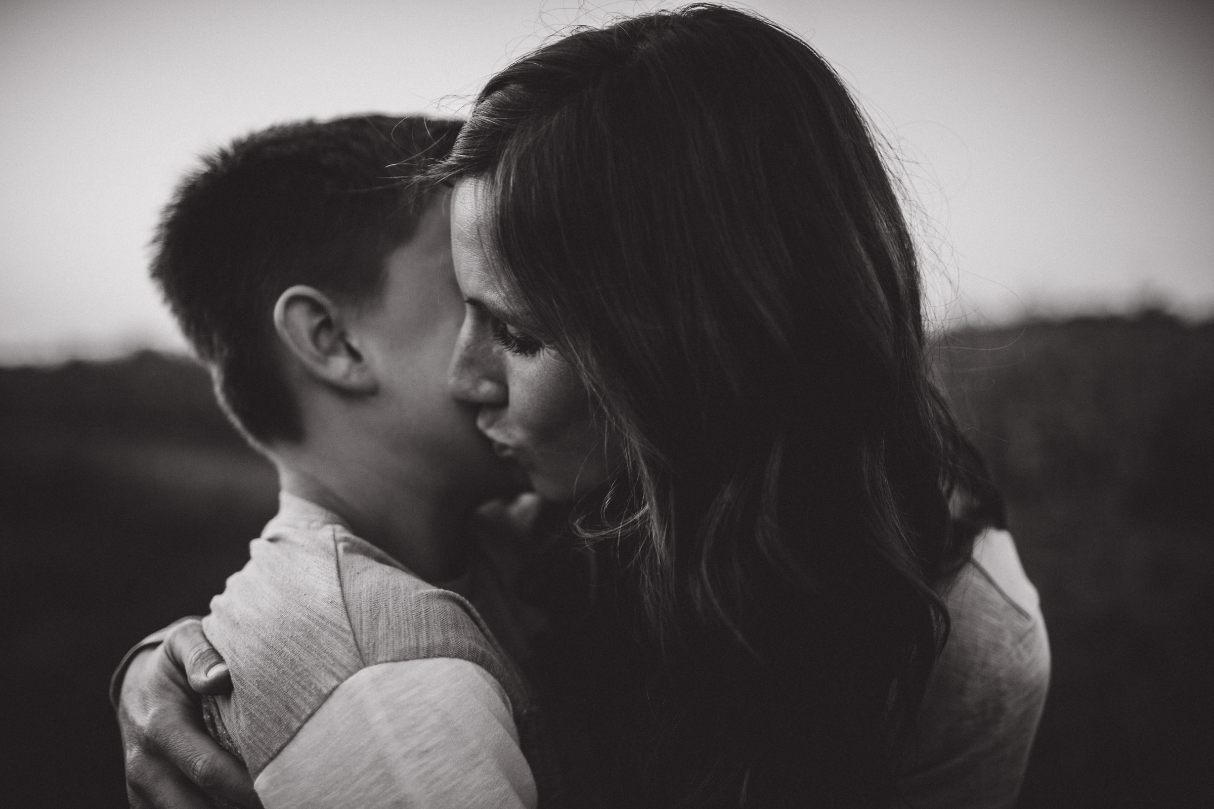 portrait of mother kissing her son, BW