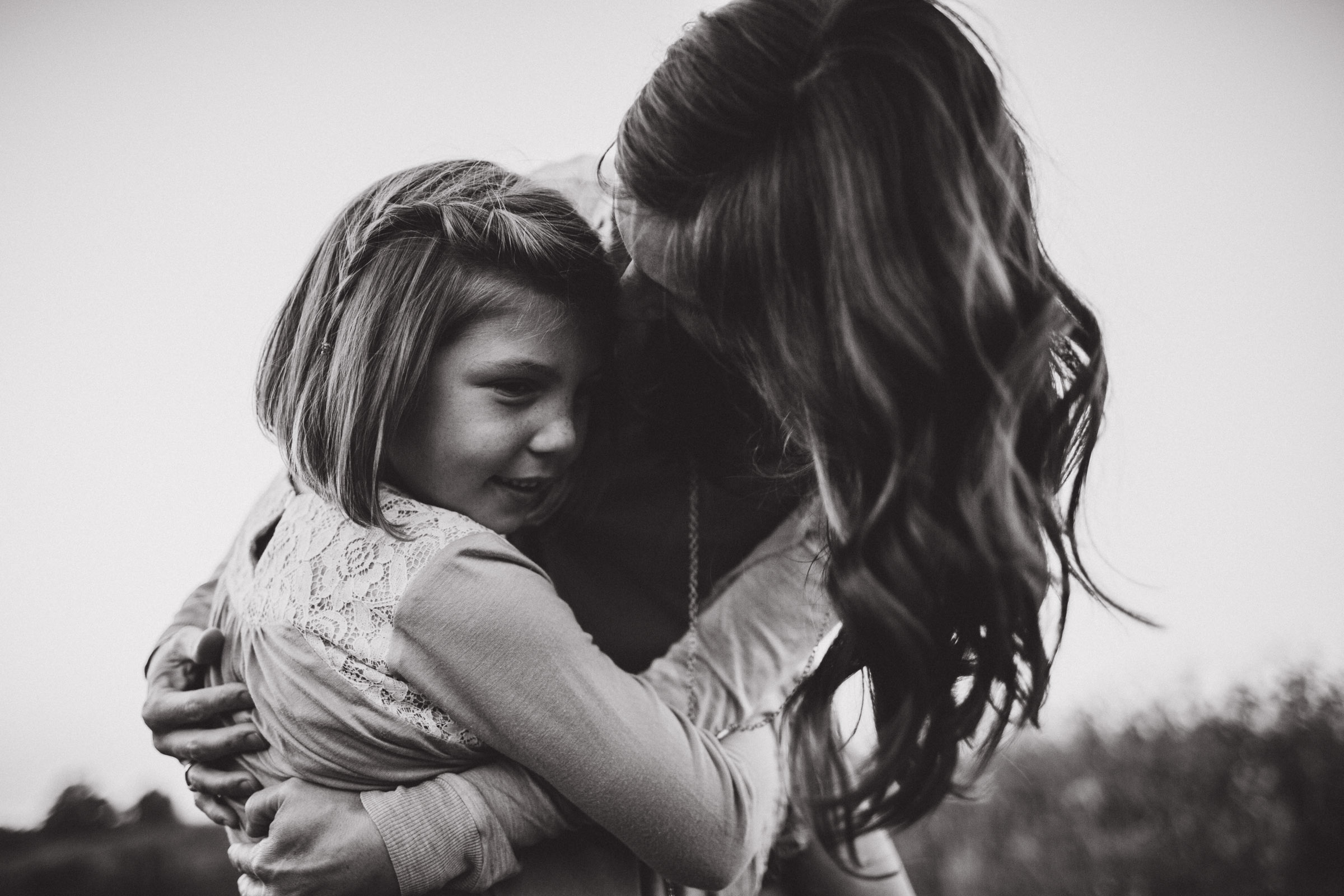 mother tenderly hugging her daughter, black and white portrait