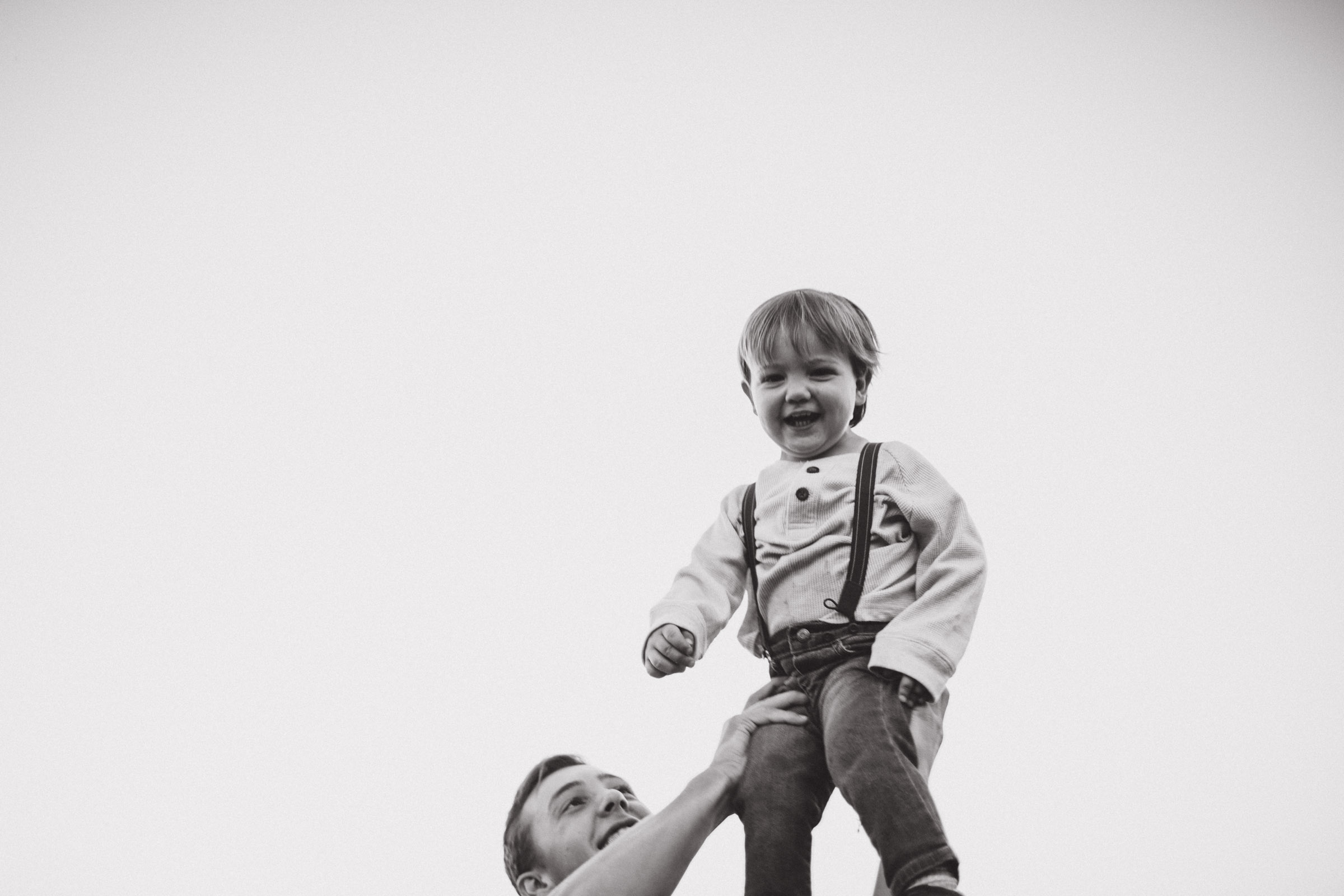 baby being held up in air by older brother