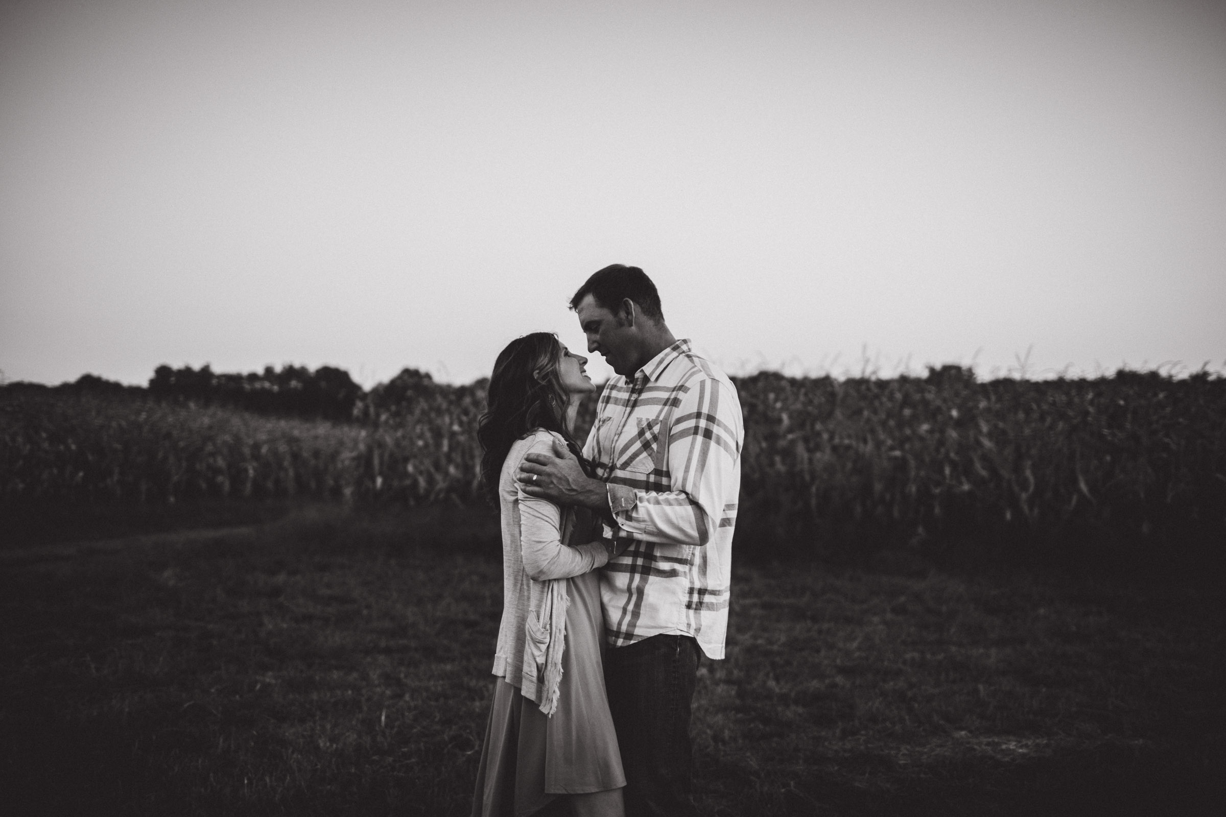 husband and wife enjoying each other in a field