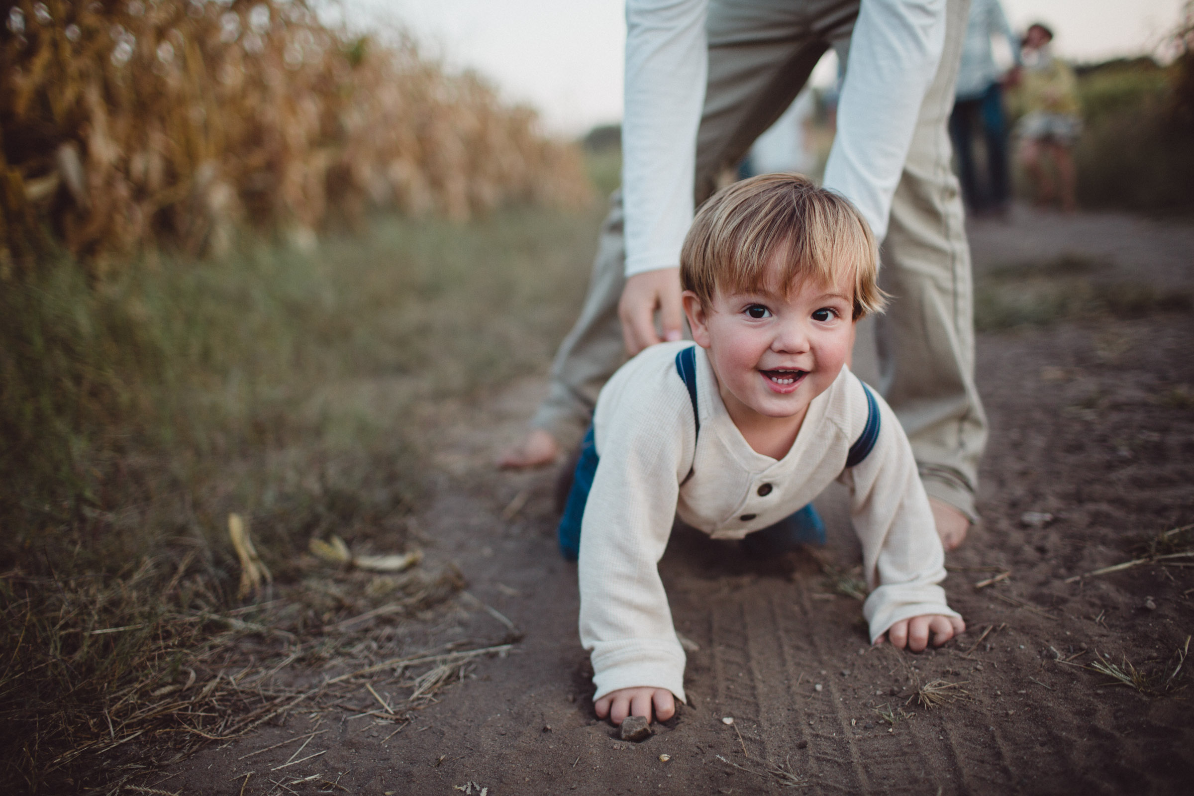 toddler looking into camera as he crawls towards it