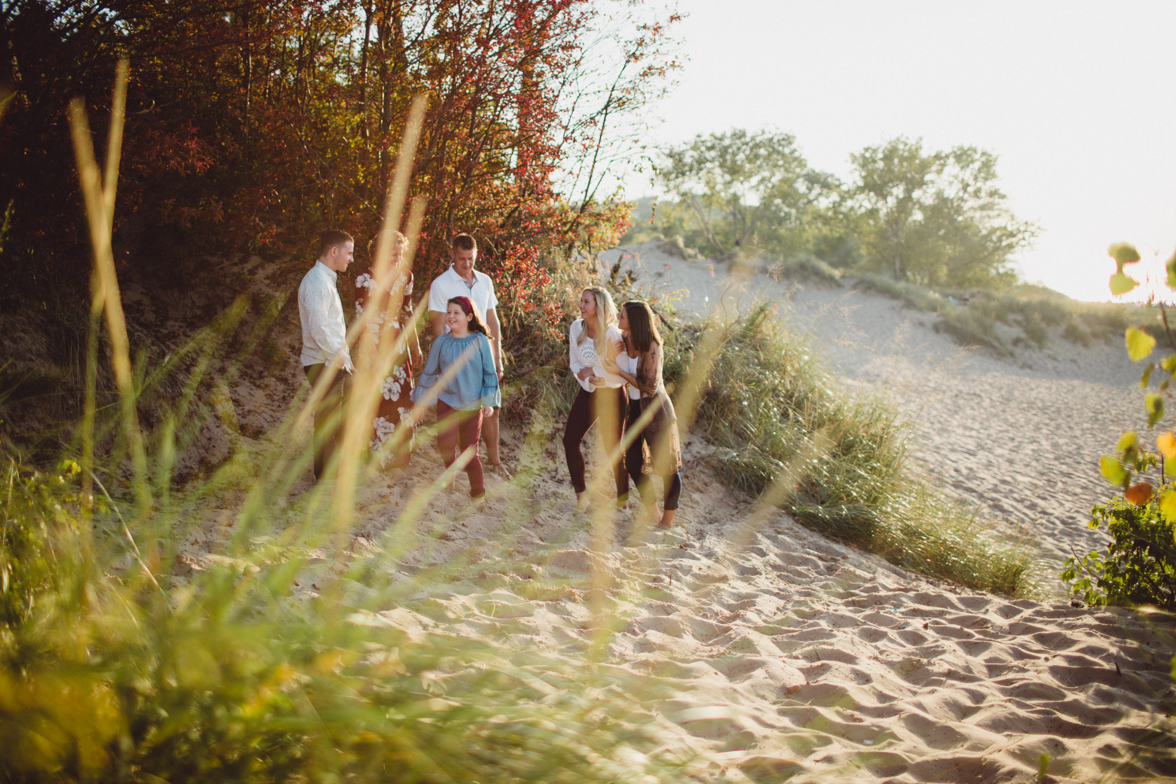 family connecting and interacting on beach, image shot through leaves
