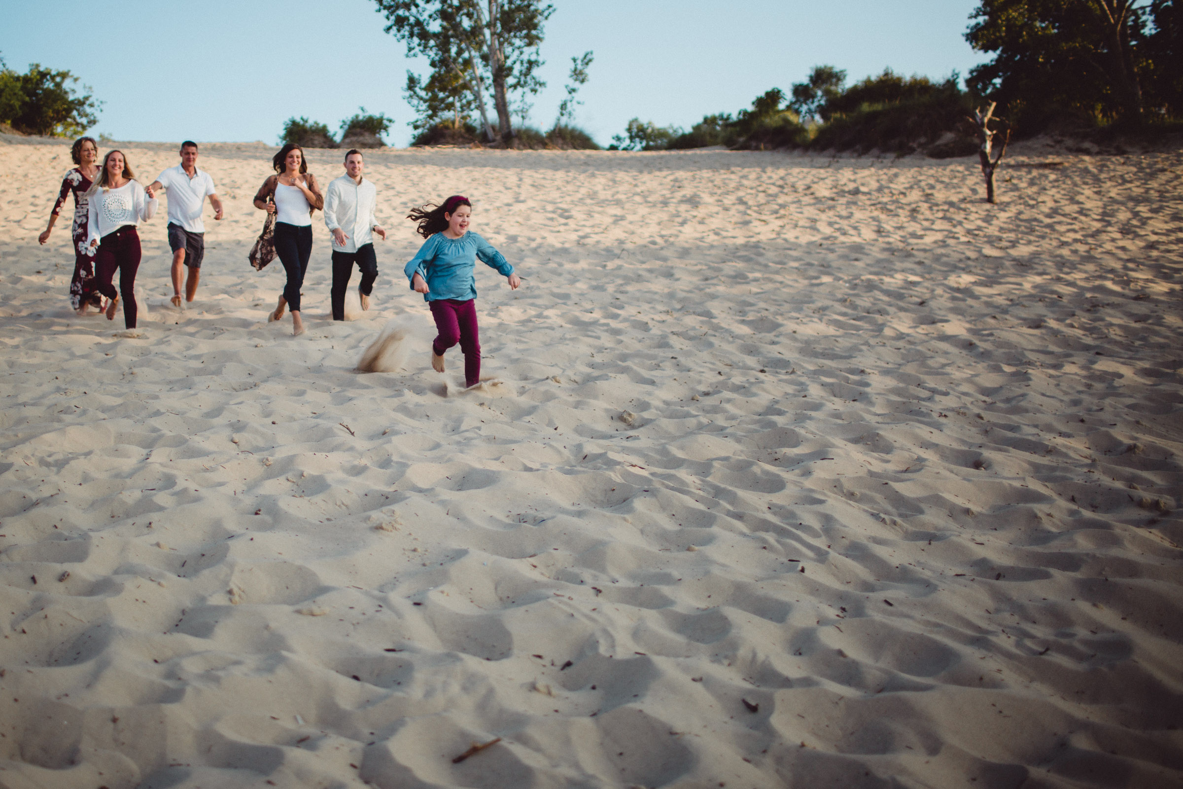 family running down a sand dune hill