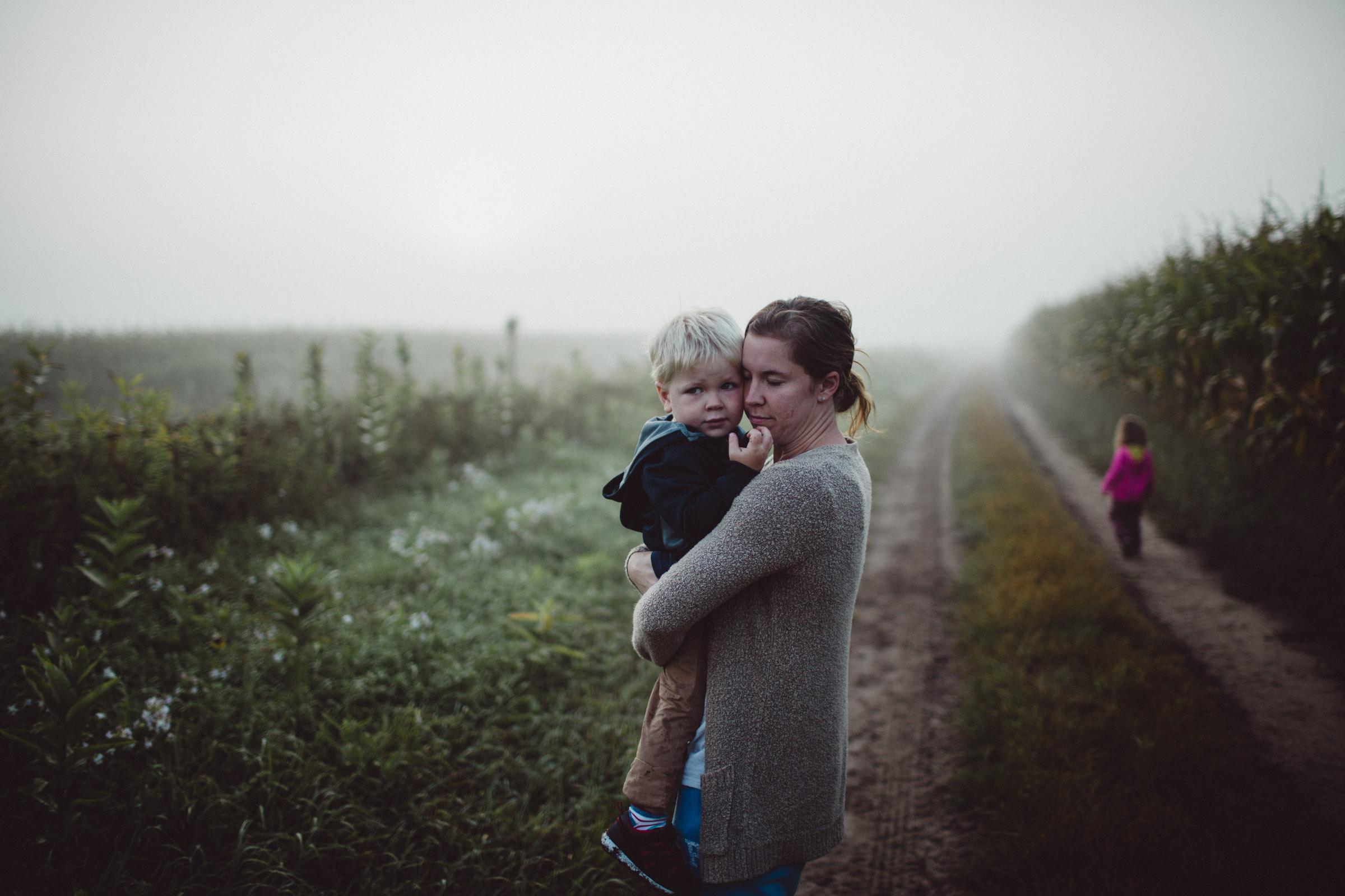 mother snuggling son in field in fog
