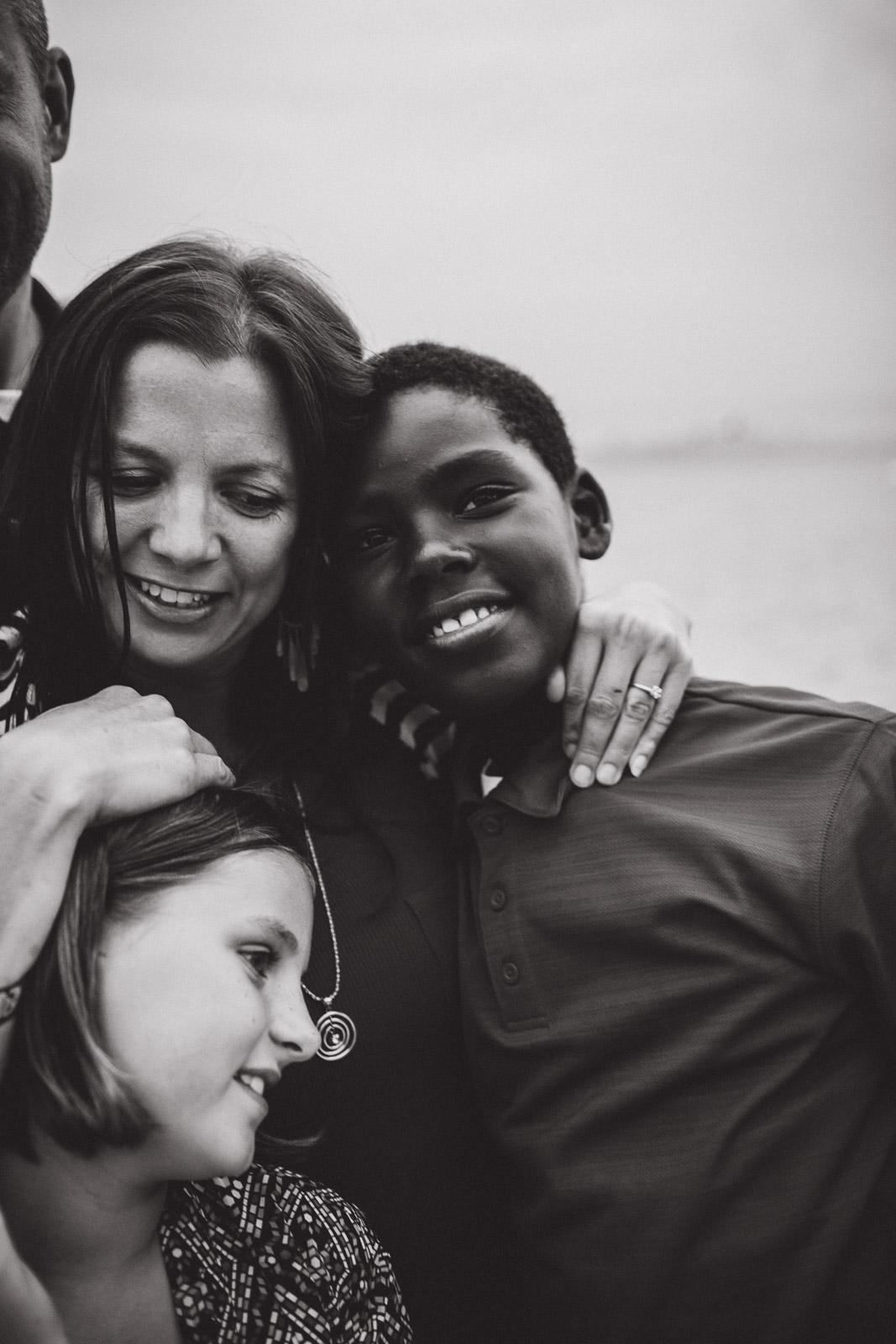 mother loving on children, black and white
