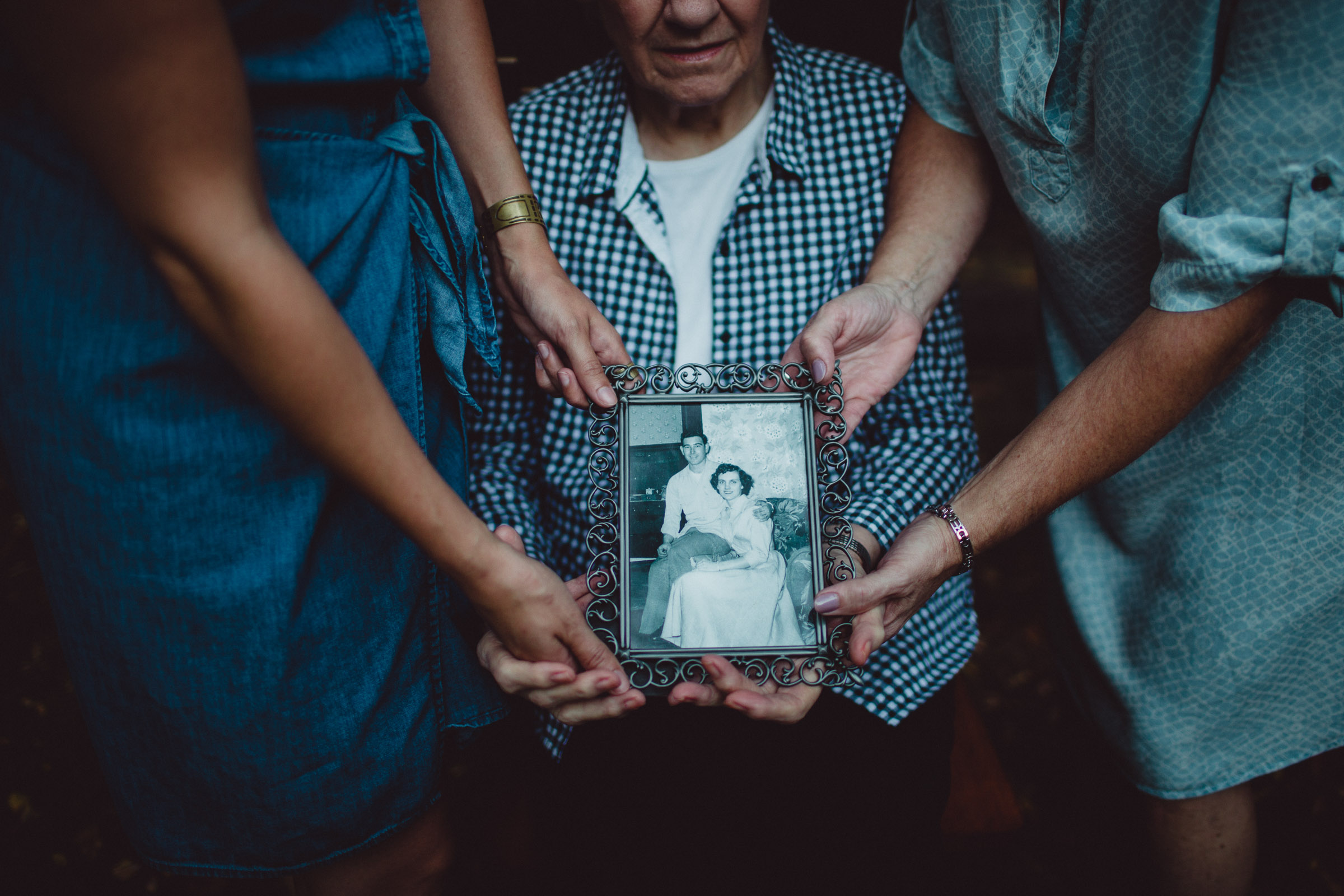 3 generations of women holding a frame of their loved one