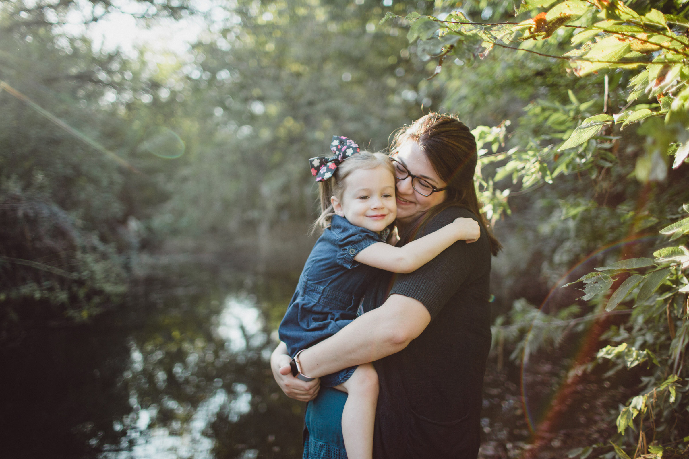 Mother and daughter snuggles in greenery within beautiful light