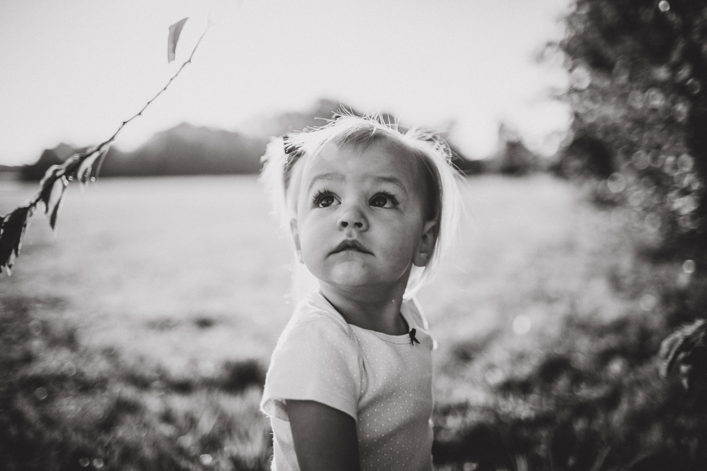 Black and White portrait of girl looking up at parents