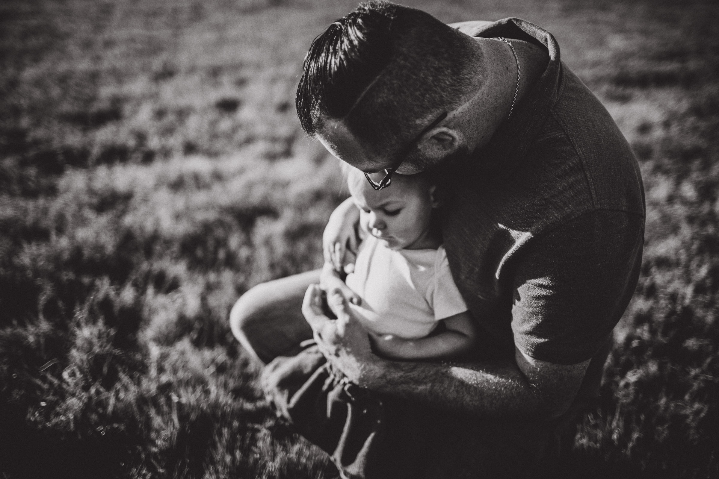 Black and white image of dad cradling his baby girl in his arms