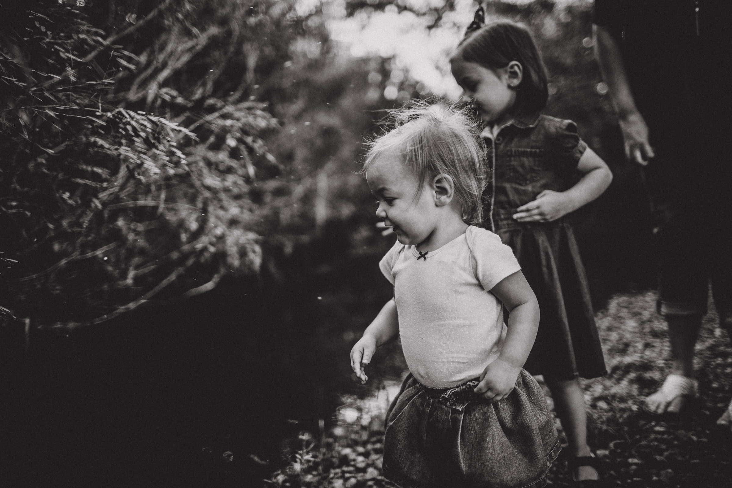 black and white image of sisters admiring a creek