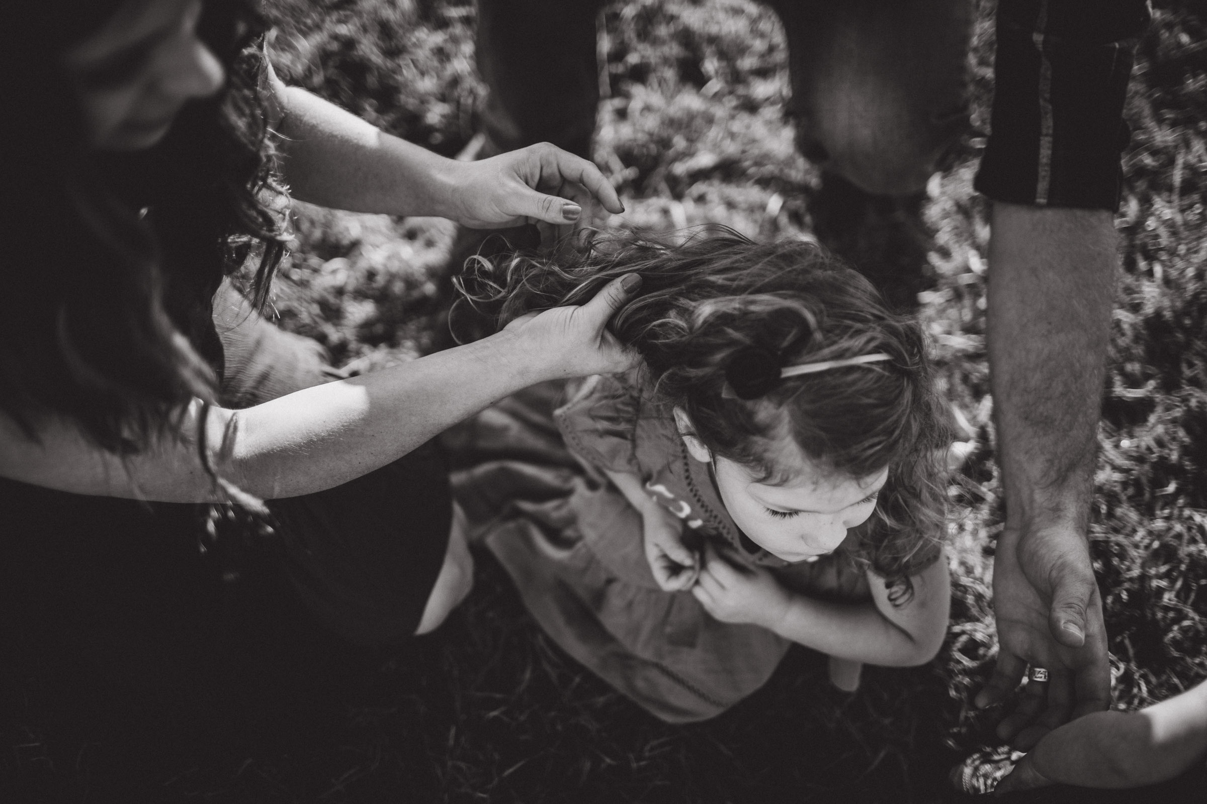 black and white portrait of mother streaming her hands through her daughters hair