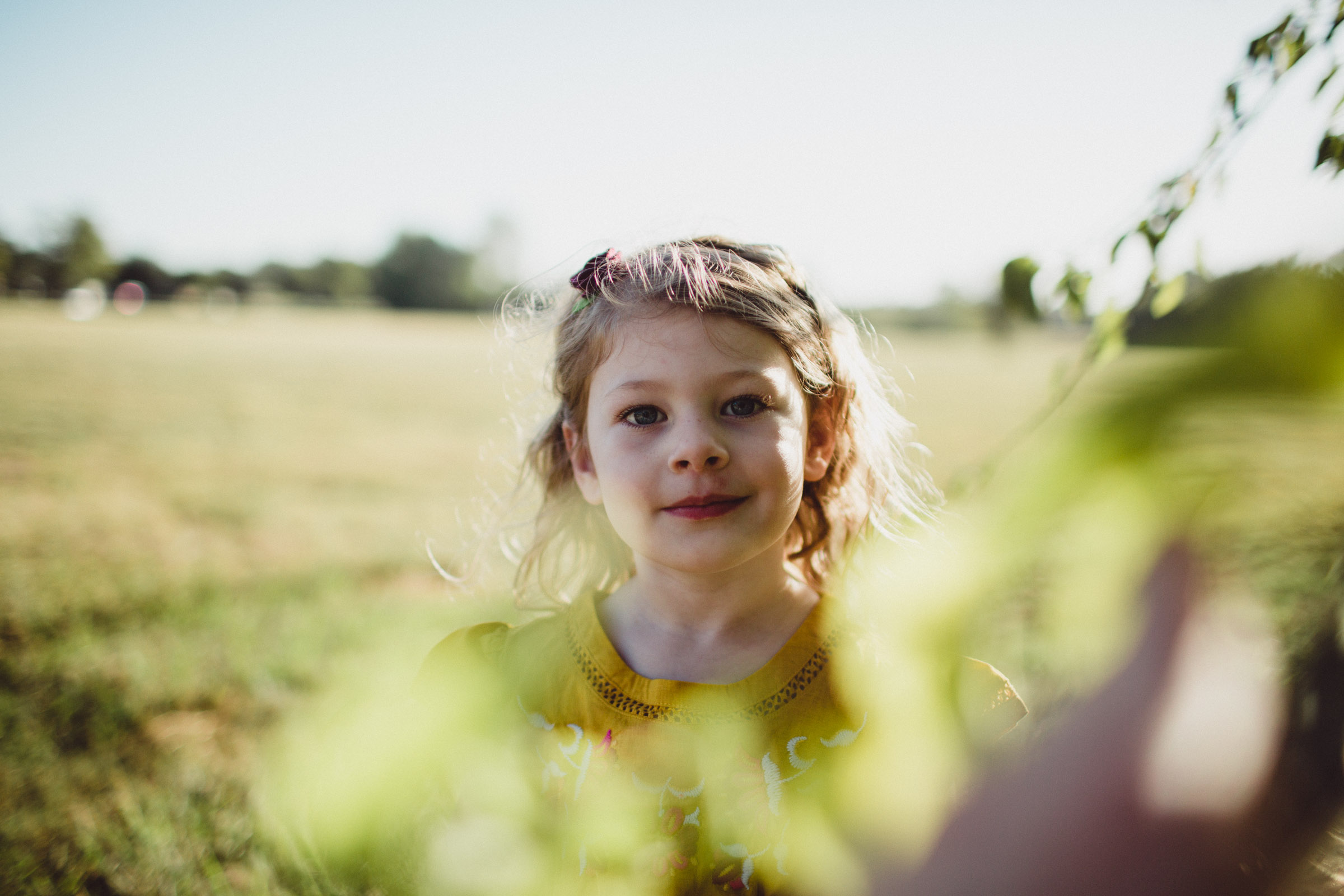 Portrait of toddler girl looking straight into camera lens through leaves