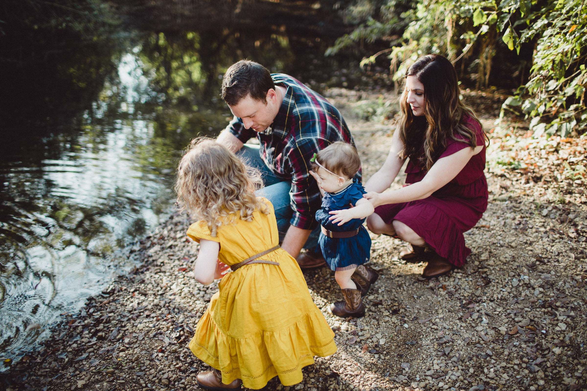 family interacting beside a creek