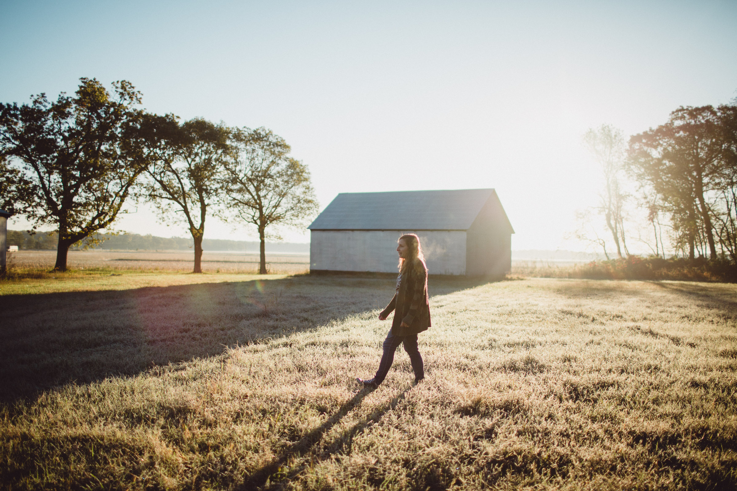 Mother walking across field, in dreamy morning light
