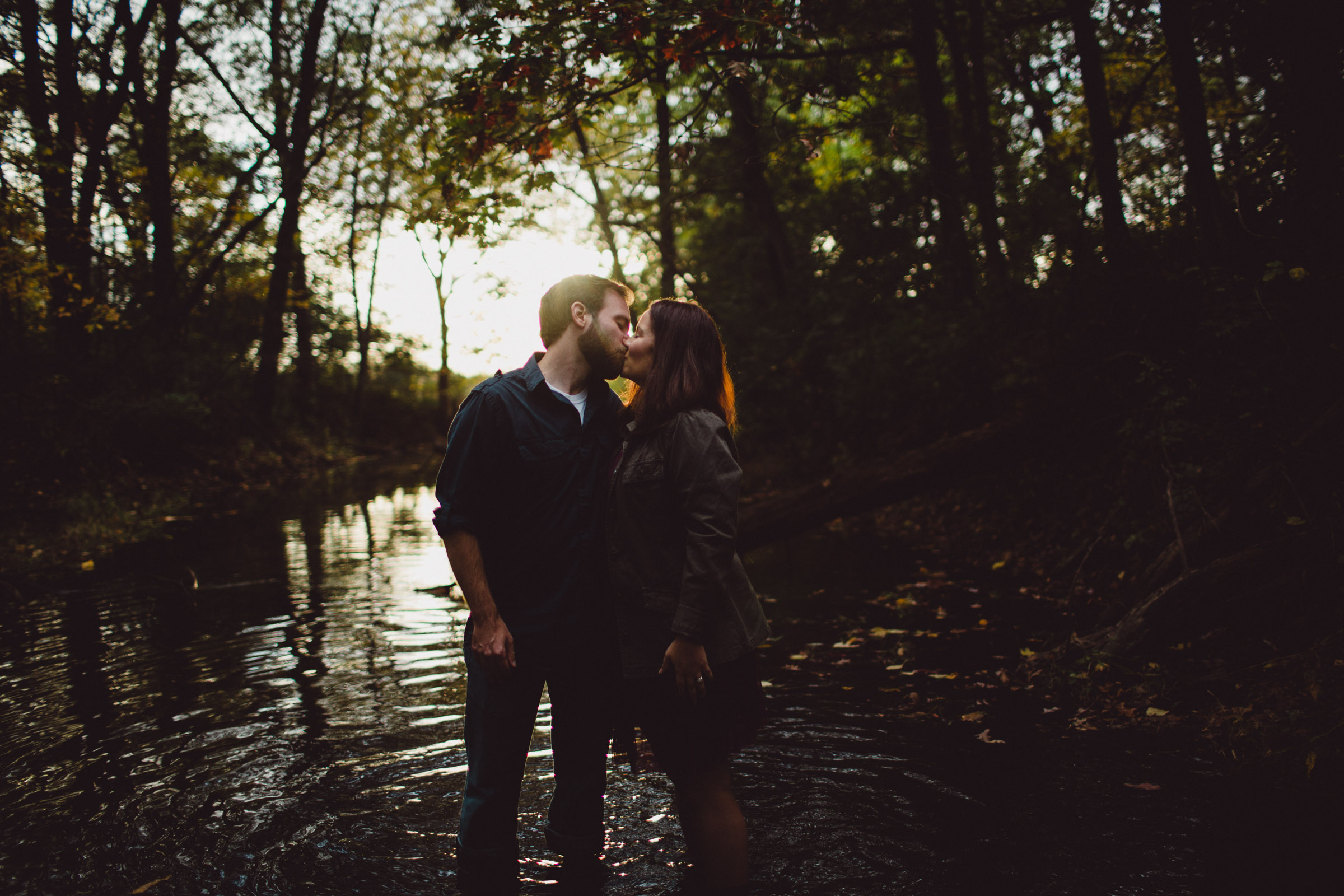 couple kissing in creek with beautiful backlight