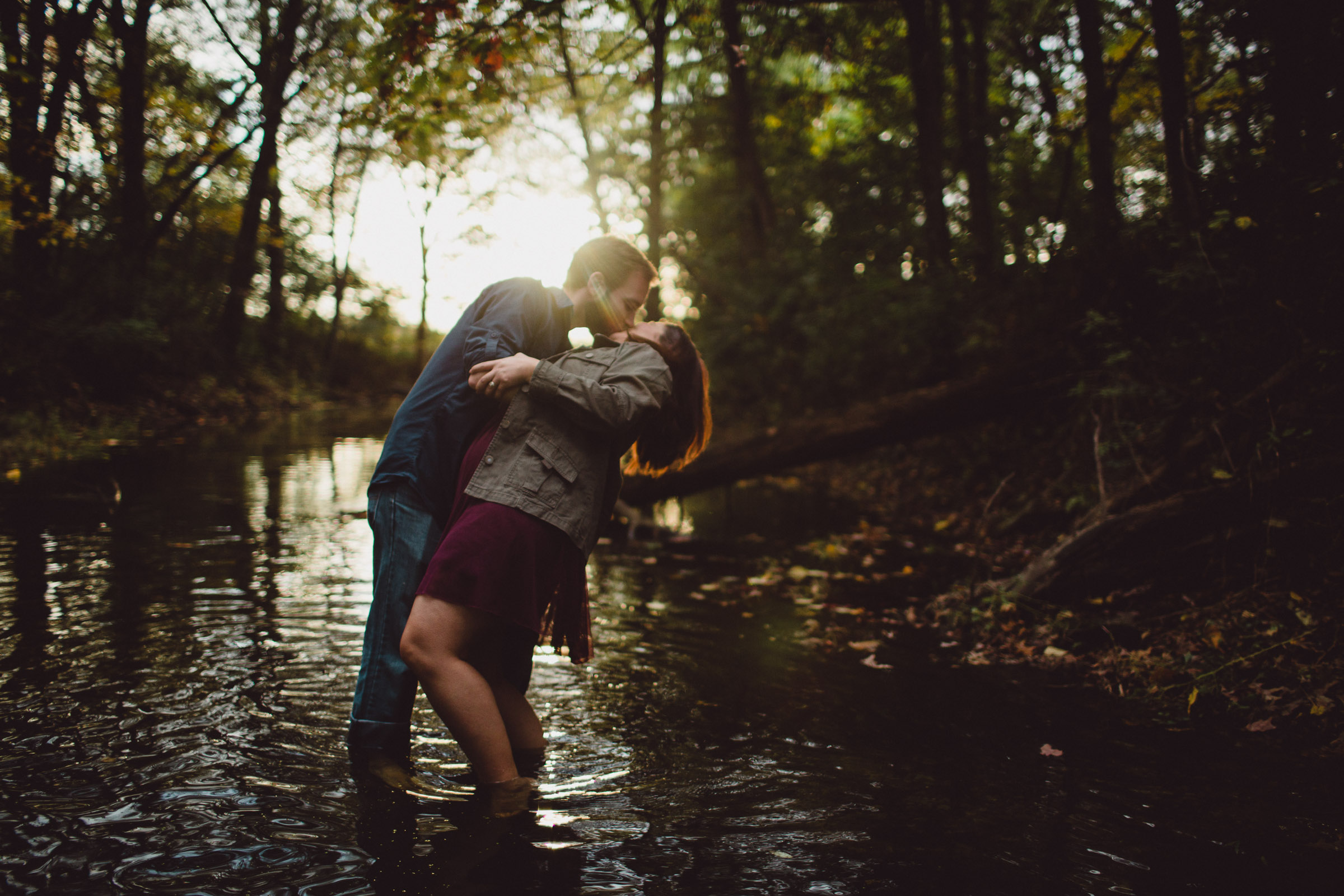 couple kissing while dipped in water with beautiful backlight