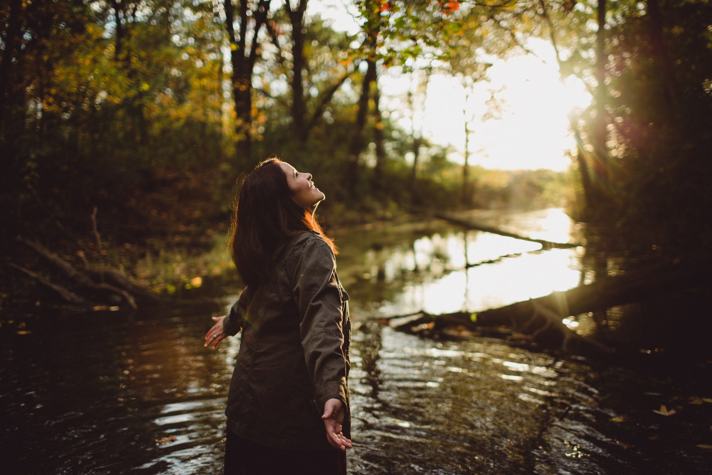 soaking in the joy and sunshine, eyes focused on the light above, girl in creek waters