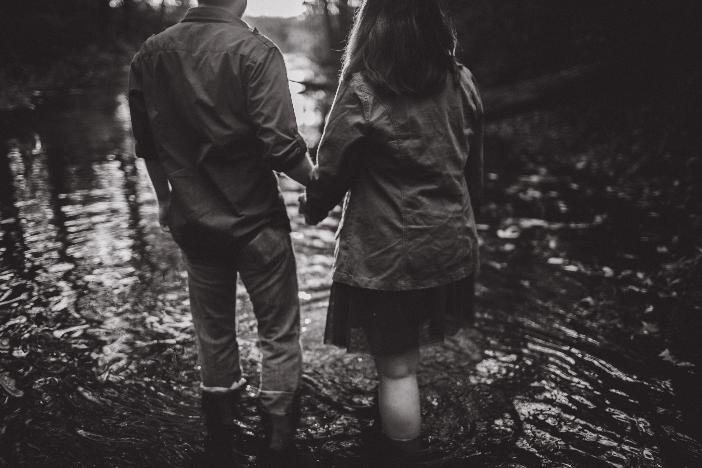 couple walking through water in creek, black and white portrait