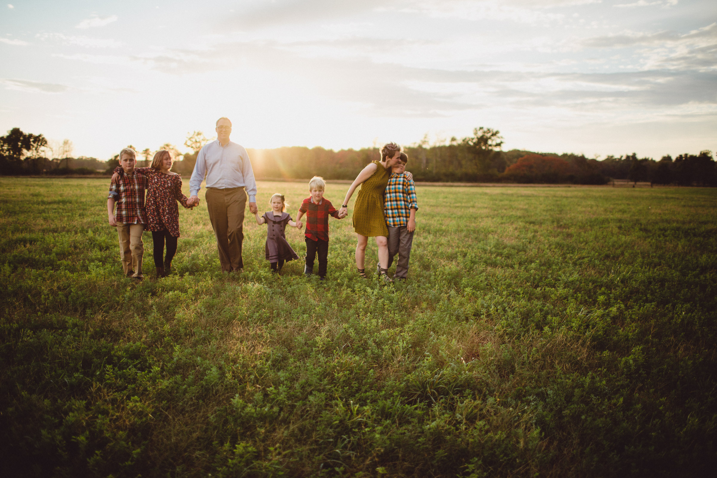 family walking together in wide open field with sun setting behind them