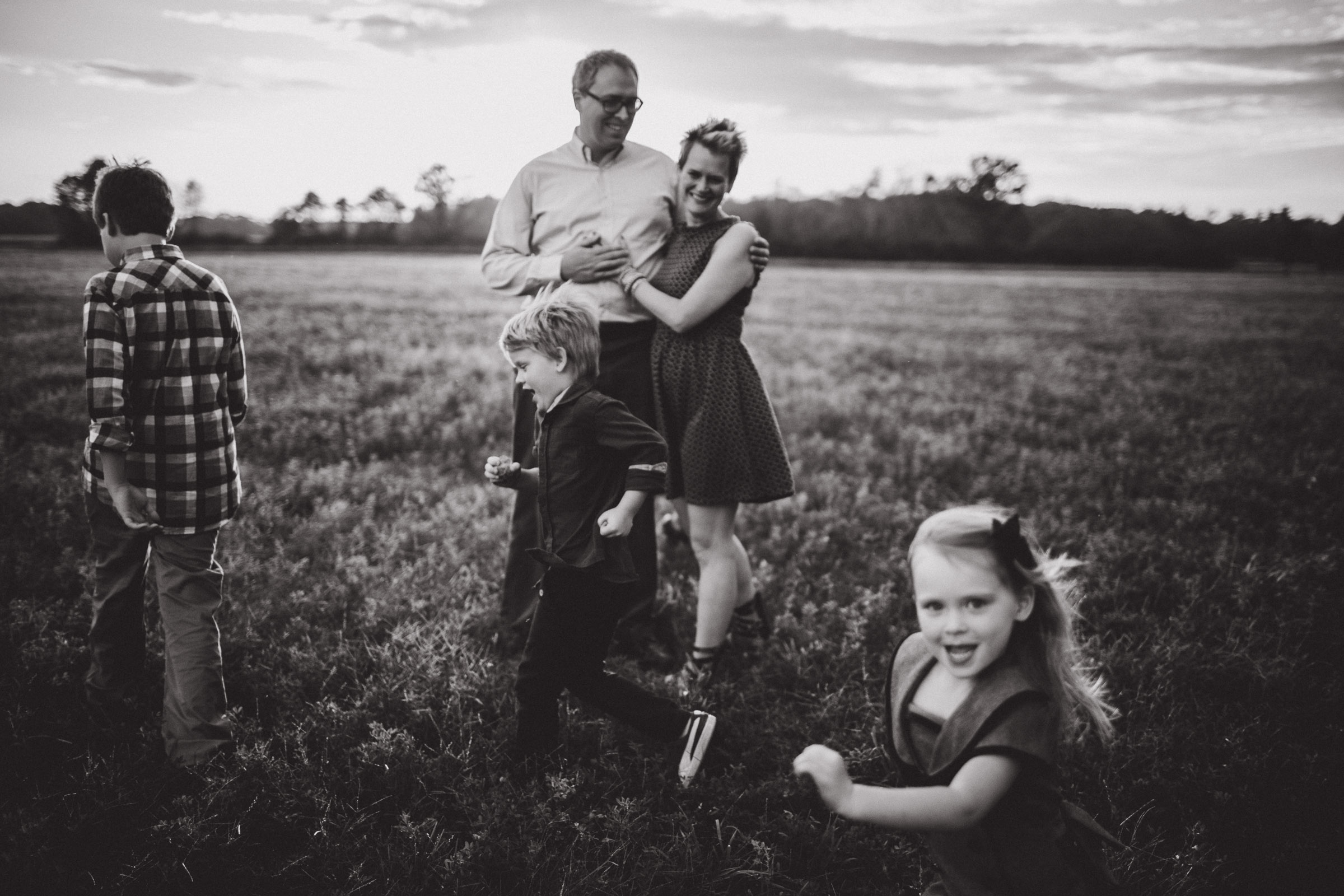 children running around parents in open field, black and white image