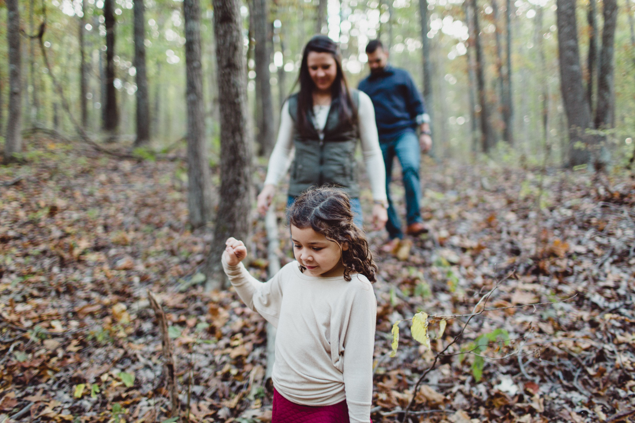 Family walking down a hill in the woods