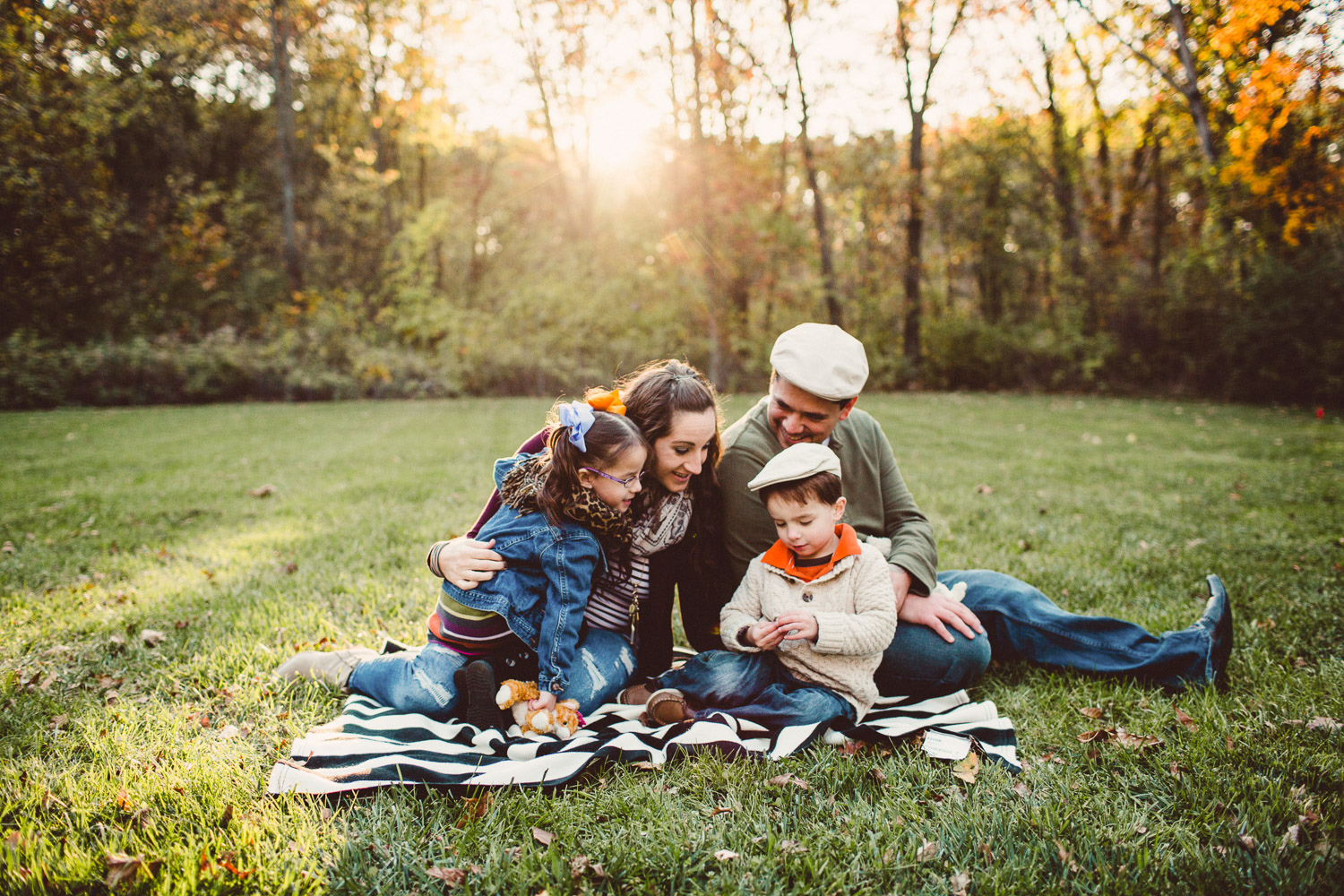 Family cuddled together on blanket with backlight