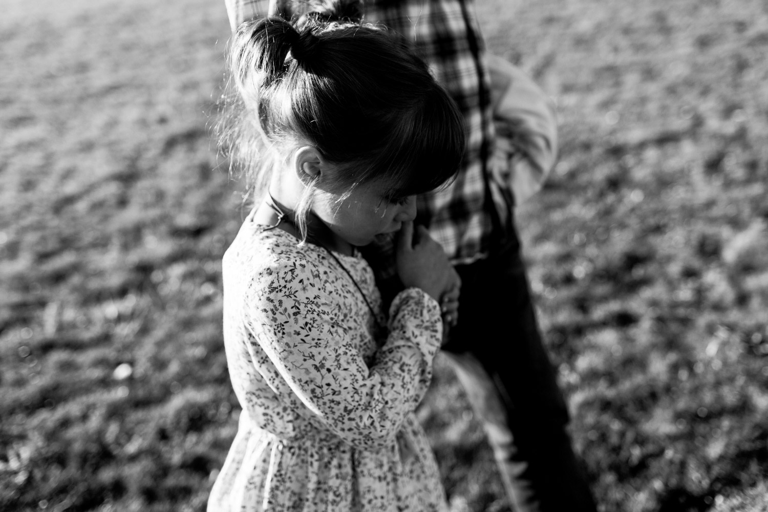 Child walking in embrace of her father, black and white portrait