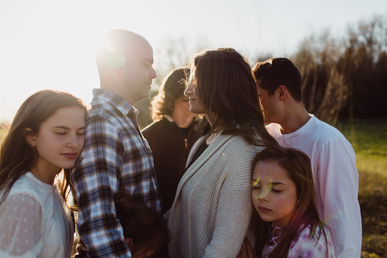 Family cradled close, in backlight, togetherness