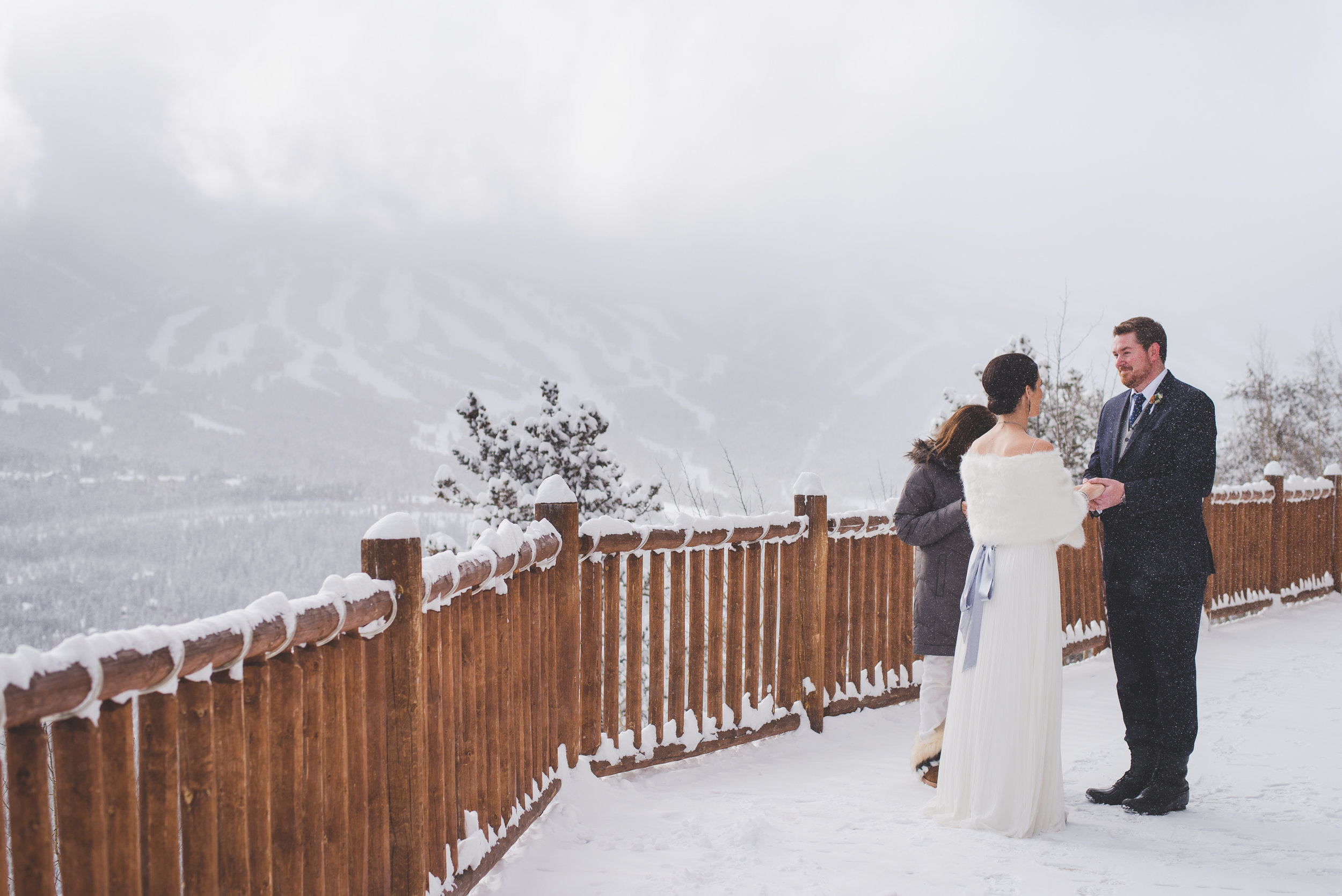 a couple elopes on the lower deck at the lodge at breckenridge, overlooking the ski runs at the resort that barely peek through the low clouds | photo by keeping composure photography