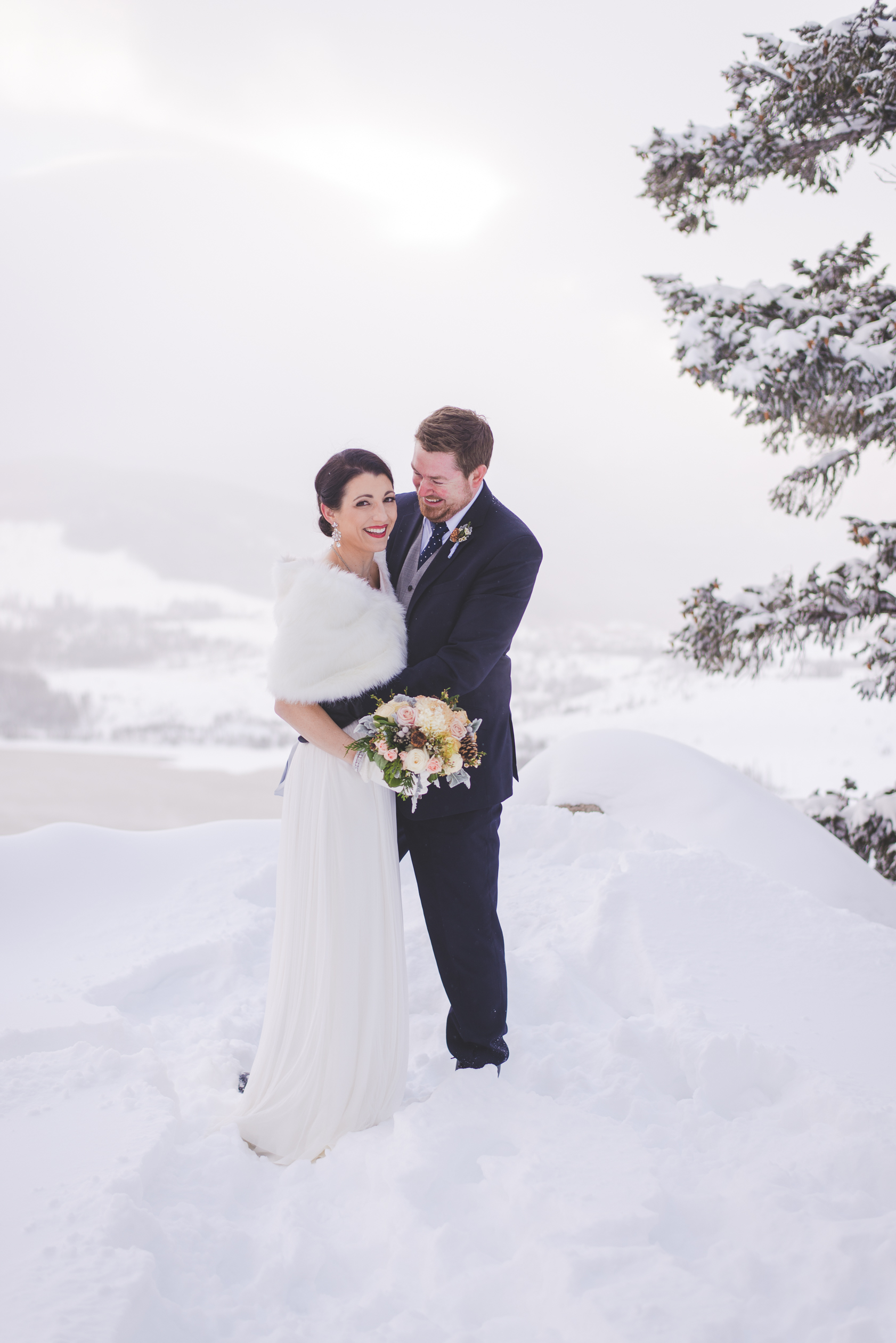 they finally made it to the overlook, where lake dillon barely peeked through the low clouds. this destination elopement was full of snow and laughter! | photo by keeping composure photography