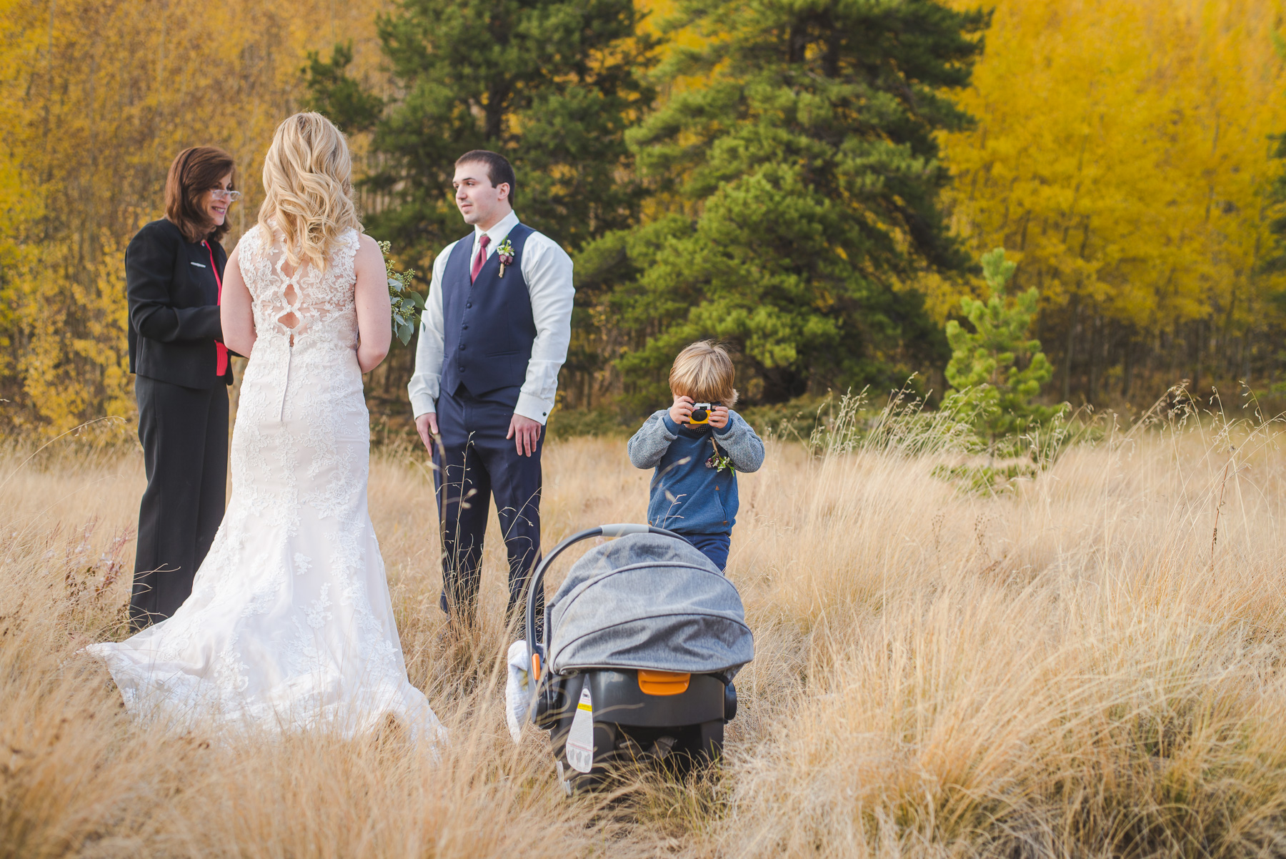 Autumn elopement in Breckenridge, Colorado | Older brother takes a photo of his baby brother in the carrier during mom and dad's wedding ceremony | Summit Mountain Weddings