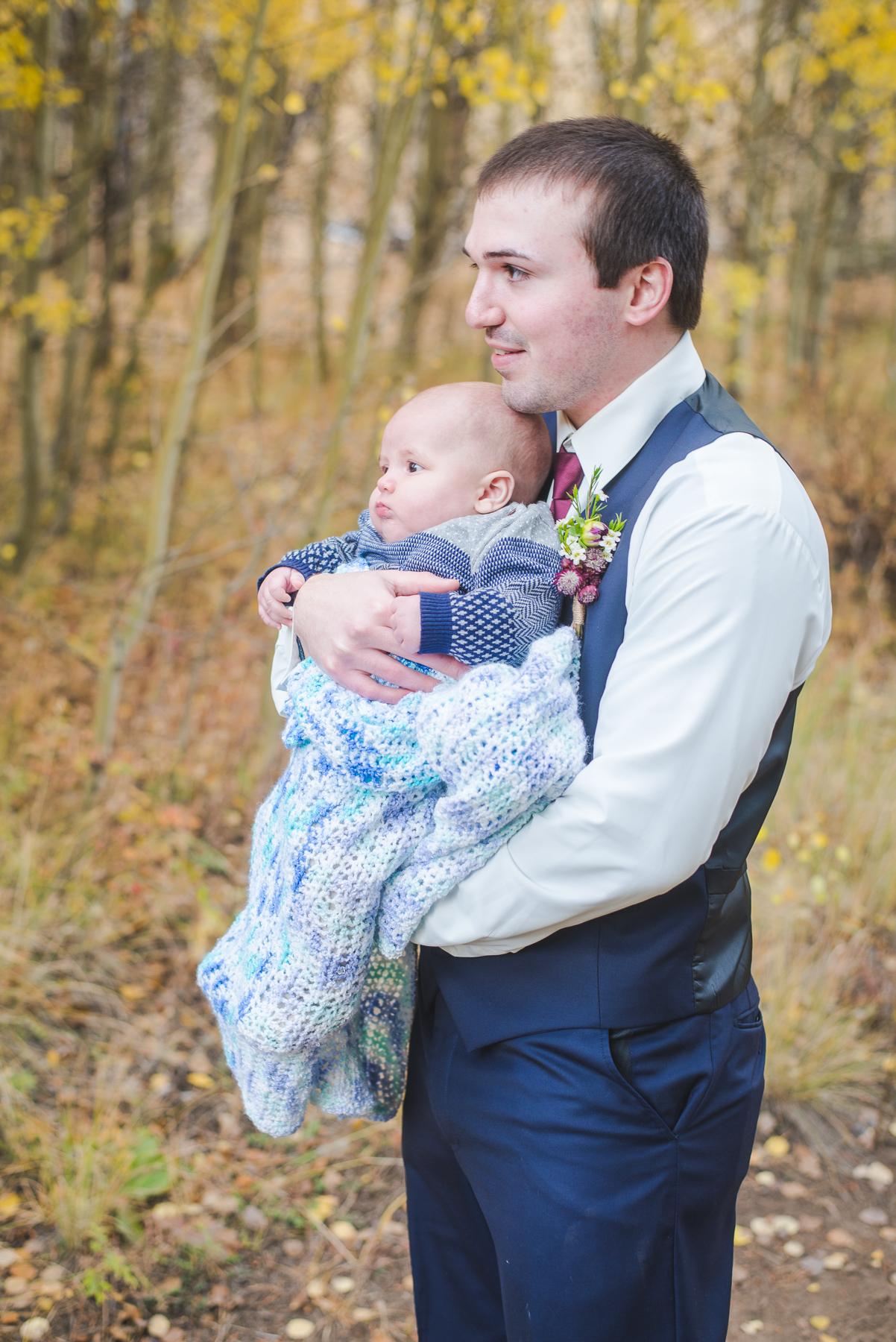 Colorado groom and young baby boy watch their bride |Autumn elopement in Breckenridge, Colorado | Summit Mountain Weddings