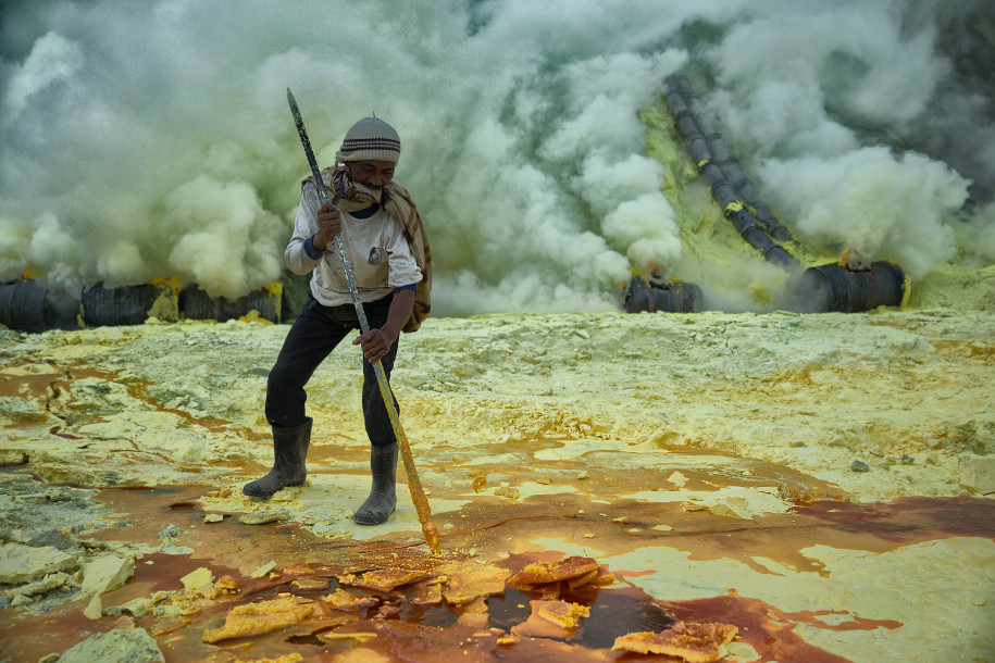 A miner chisels out chunks of sulphur as he readies his basket to carry out of the bowels of the Ijen volcano.