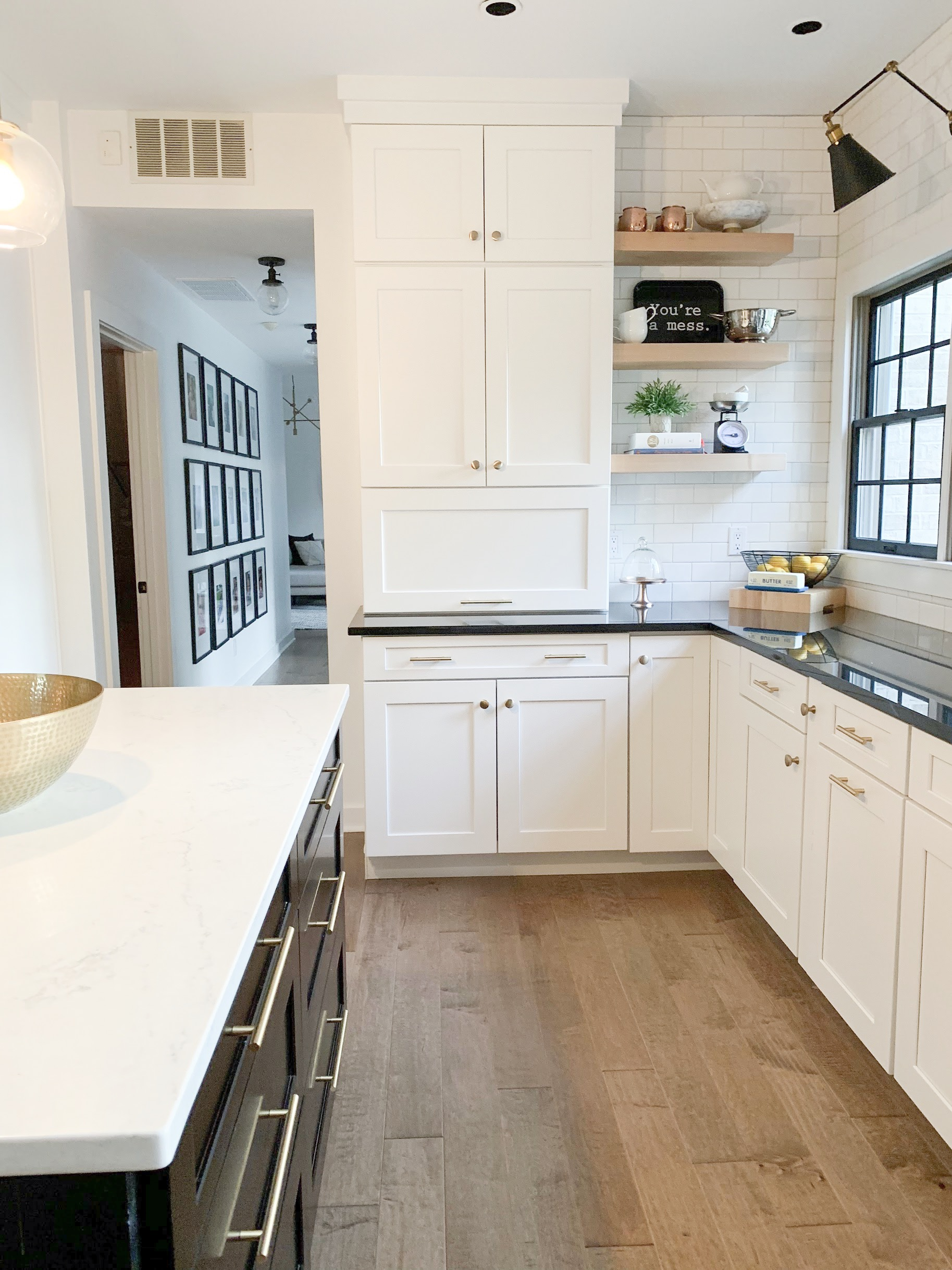 black and white kitchen with wood floors and white subway tile