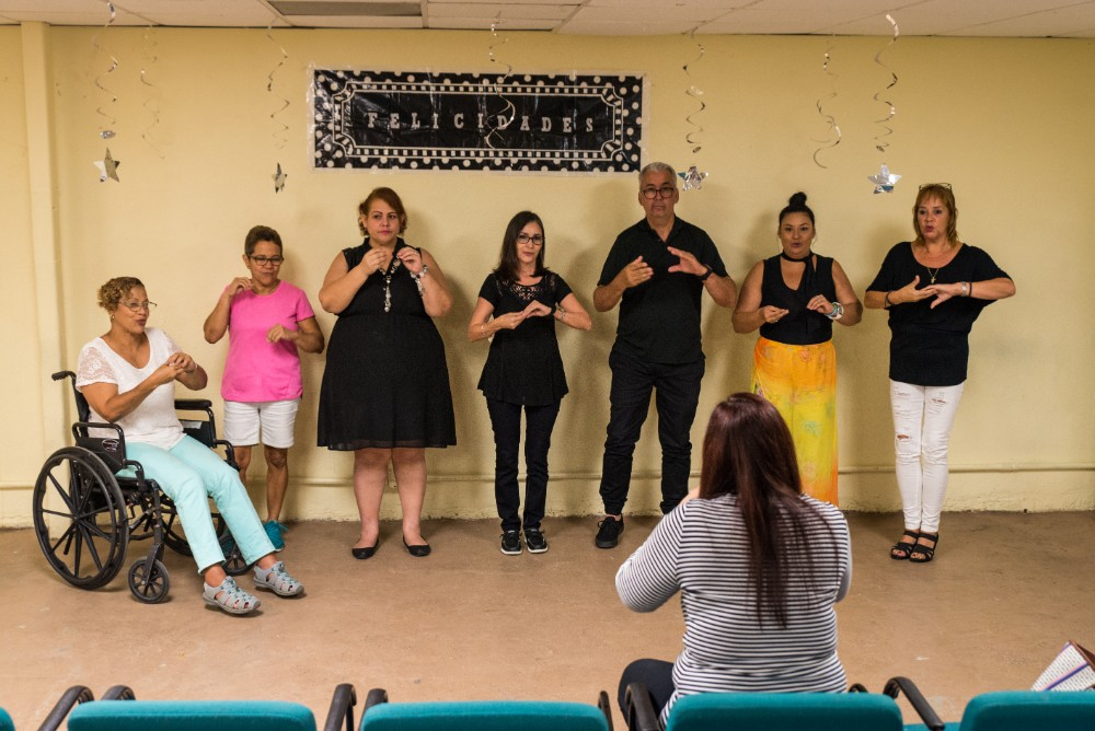 "Sign language students sign the lyrics to ""Había un Sapo"" during their class graduation ceremony at the MAVI office."