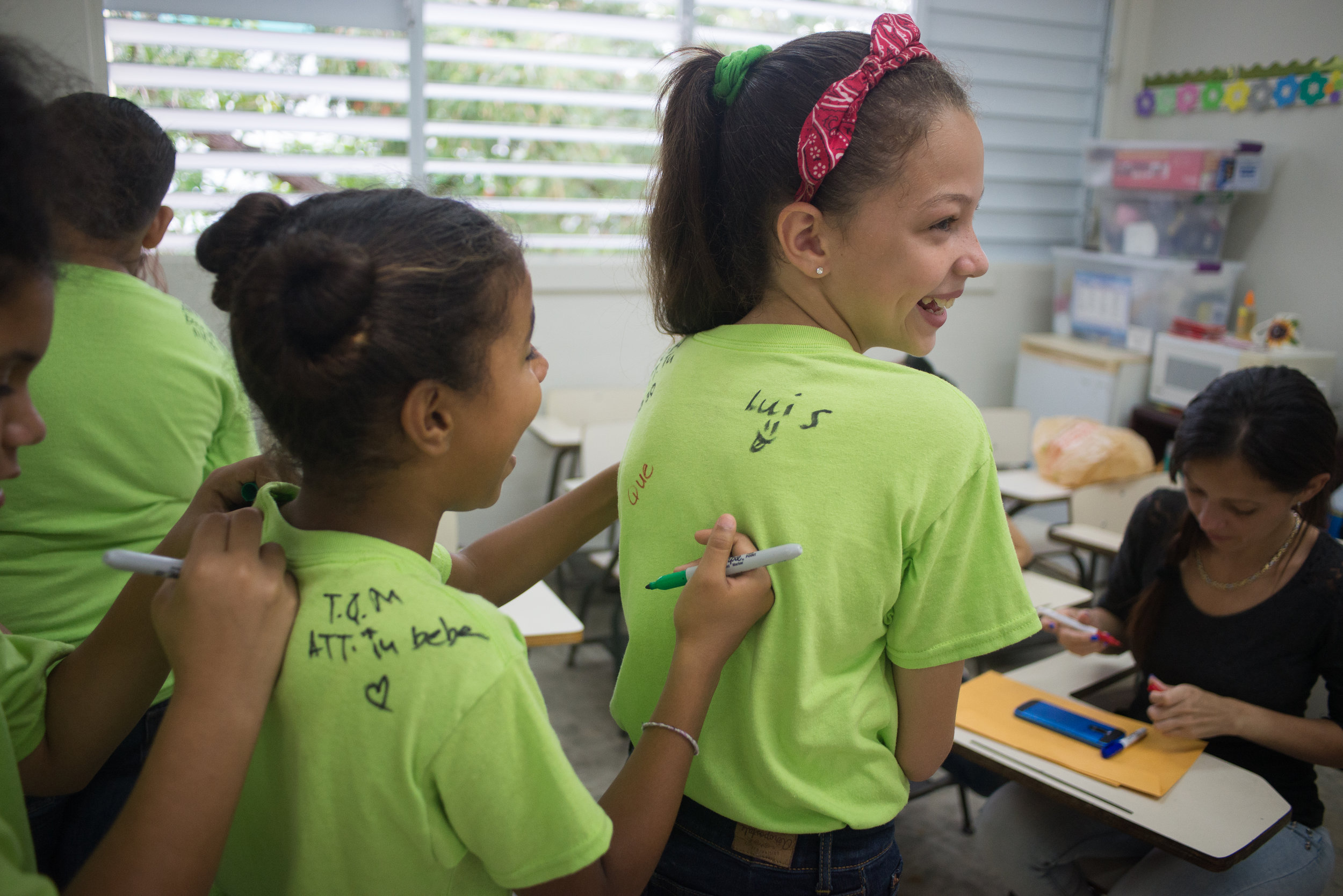 6/6/18 – Bayamón, Puerto Rico – The Puerto Rican Department of Education is closing 283 schools, and moving multiple schools into the same building, citing the past year's drastic drop in enrollment as one of the primary reasons to lower the amount of schools, and instead increase the amount of students in each school. Students of special education schools are one of the groups to be most negatively affected by these closings, as the new schools may not offer the resources the students need and have access to at their current schools. La Escuela Aurelio Perez Martinez in the town of Bayamón is among the schools that will be closed. Sfudents in 4th and 5th grade sign each others' shirts on the last day of the school year. (Sofie Hecht Photography)