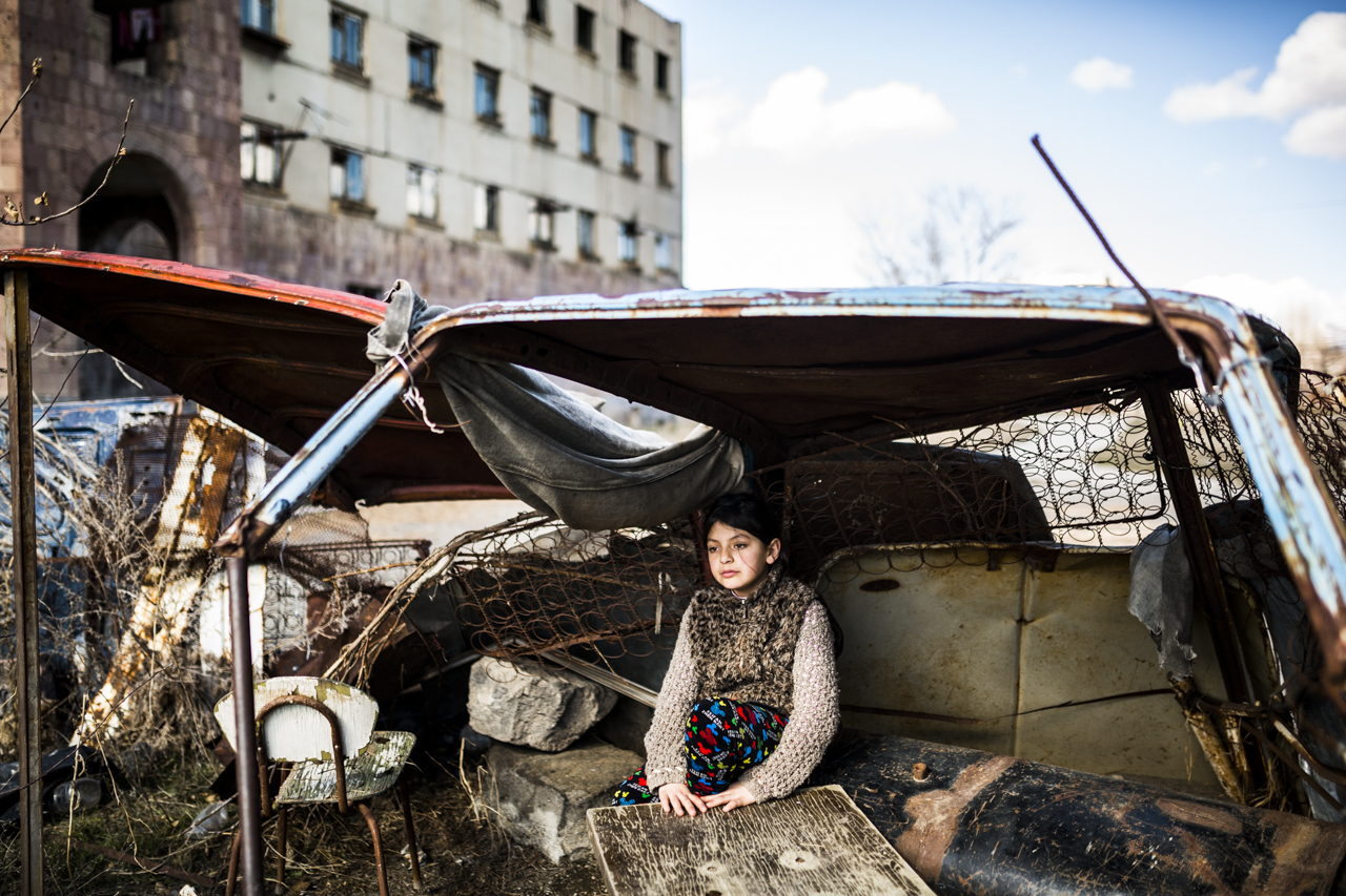 """Syuzanna (9) sits in a """"shelter"""" made of old car rusty parts in front of the abandoned building she lives in. Ten days ago her father committed suicide, as people say, because of the debts. Photo by Yulia Grigoryants."""