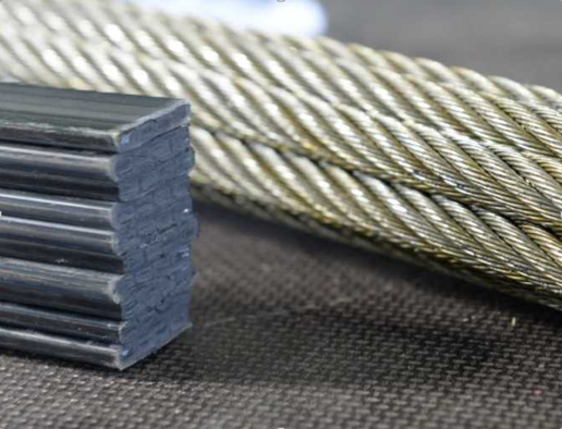 Figure 2. A section of Kone UltraRope sitting next to traditional steel cables.