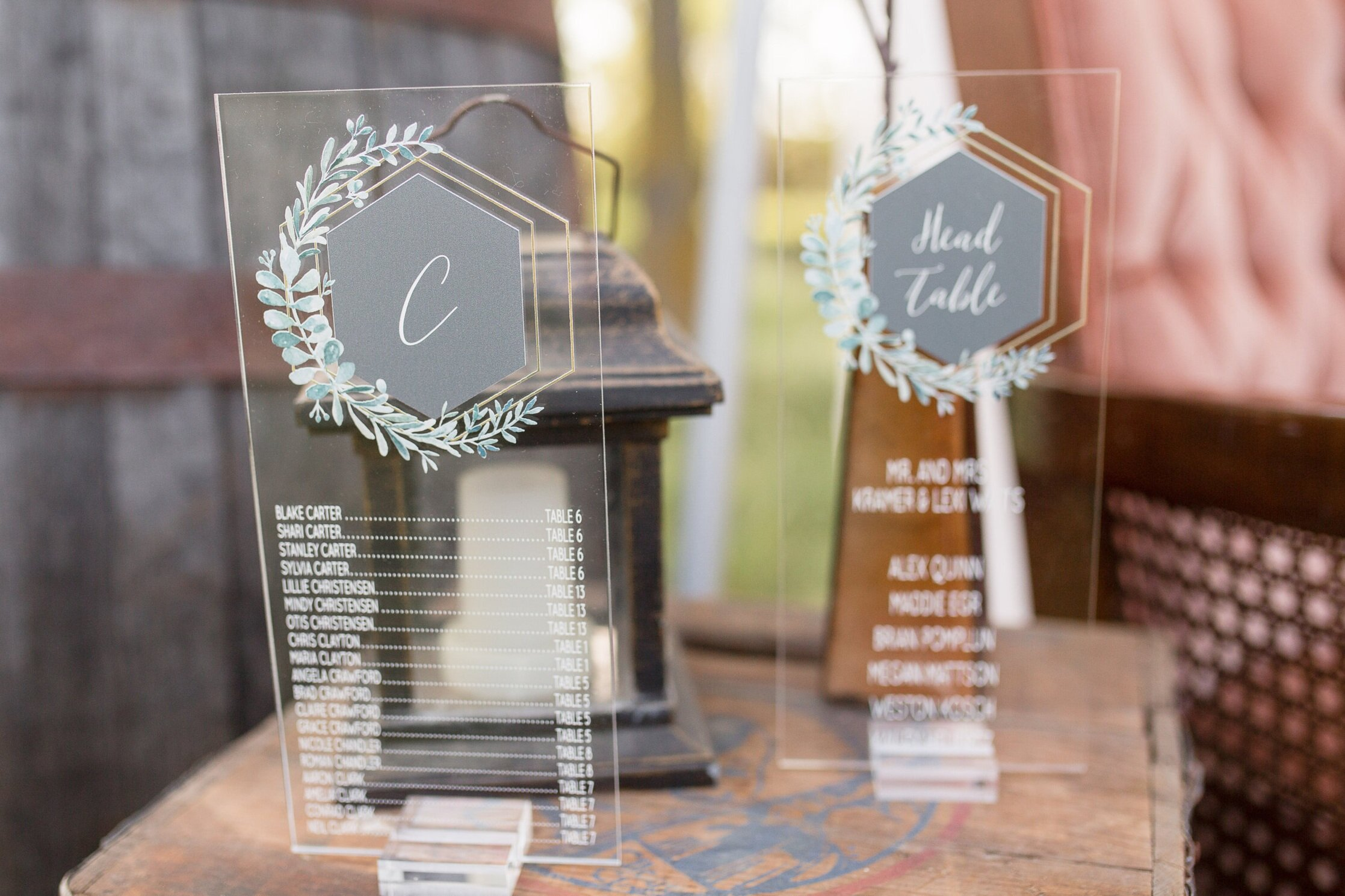 acrylic seating chart with gold hexagons and greenery