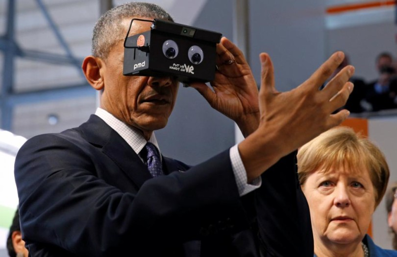 U.S. President Barack Obama tries virtual reality glasses as he and German Chancellor Angela Merkel (R) tour Hanover Messe Trade Fair in Hanover, Germany April 25, 2016. REUTERS/Kevin Lamarque