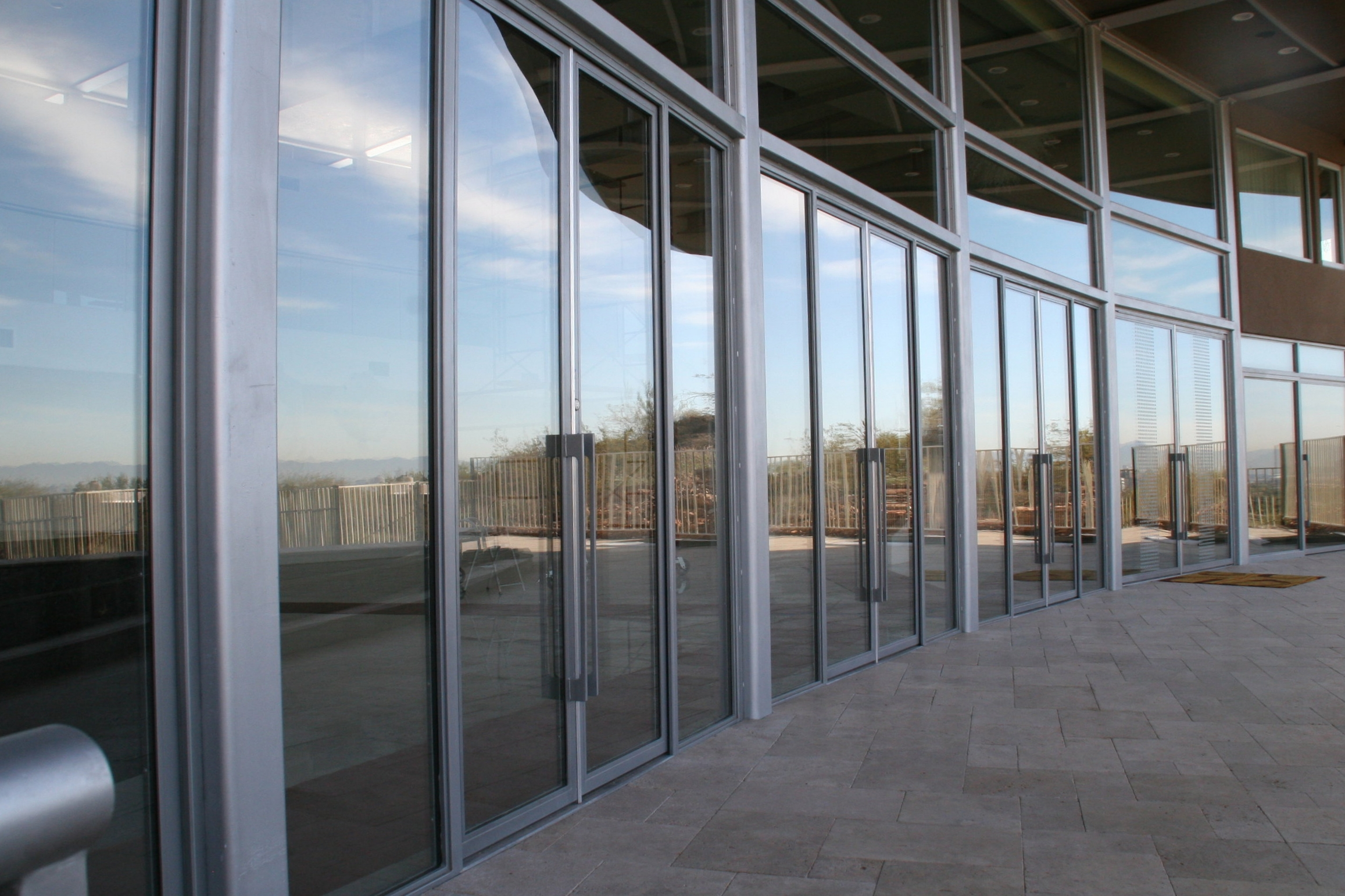 COMMERCIAL IRON AND GLASS DOOR 11  Our steel and glass doors are engineered to virtually span any height. A segment of this extensive wall of steel and glass doors and windows brought power, light and beauty to the front elevation of this contemporary project.