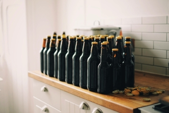 Unlabeled beer bottles with yellow caps on a table in hipster apartment