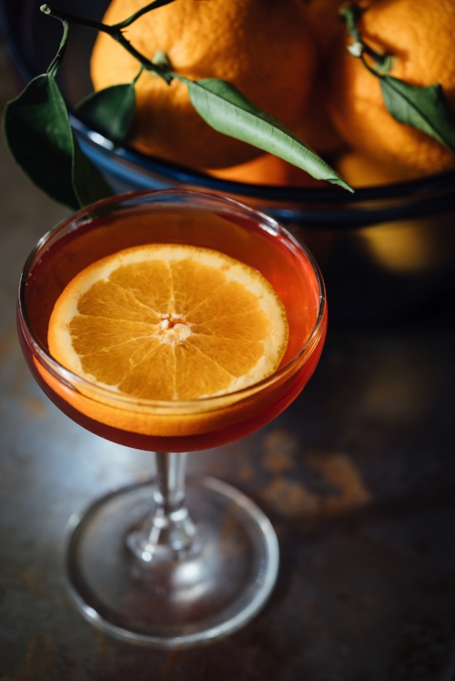 Orange campari cocktail with orange slice in coupe glass next to glass bowl of oranges
