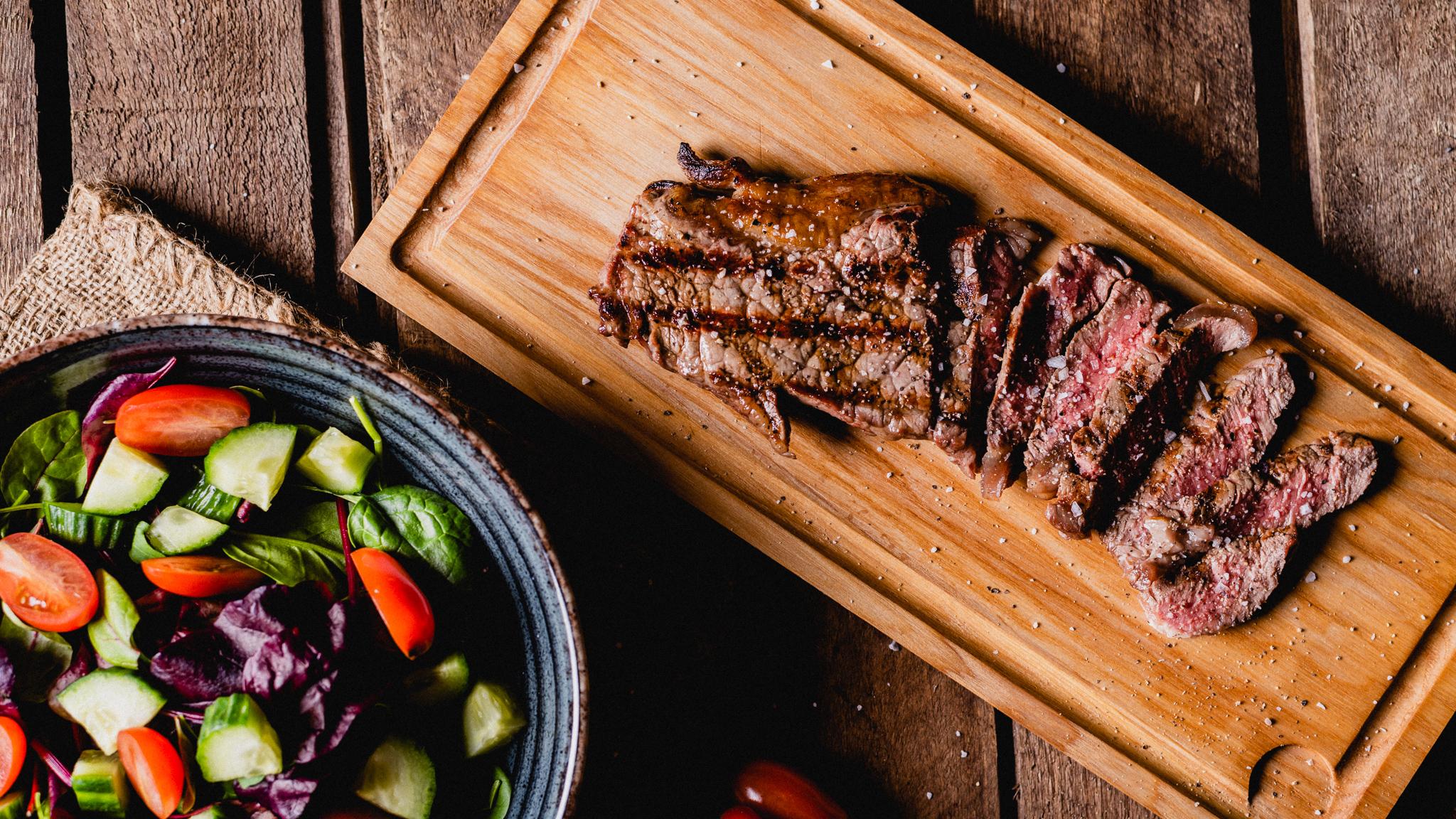 Steak salaten med en grillet sirloin steak på ca. 180 gram, lagt over sprød salat med tomater, hjemmebagte croutoner, agurker, valnødder, og soltørrede tomater.