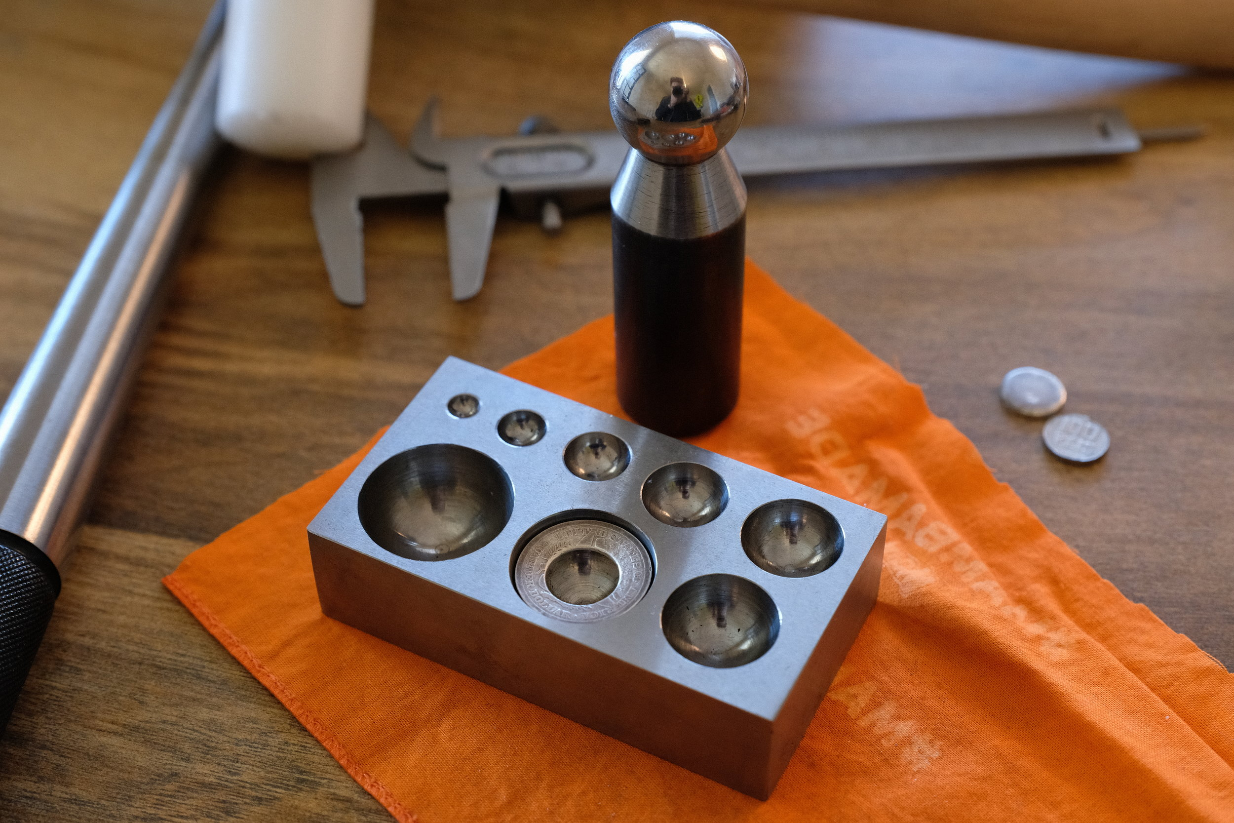 The coin-donut is placed in the dapping block to taper the ring-to-be. The side that will face out goes down.