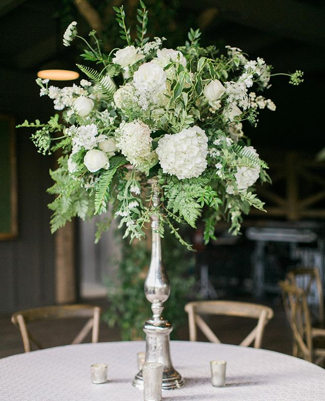 As the temperatures cool and nights grow longer; we smile as we reflect on the many flower filled days of summer. This arrangement of mixed #naturalgreen & #white flowers will remain one of our favorites for years to come. Beautiful image by: @almondleaf . . Planning: @thewholeshebangevents // Venue: @theeseeolalodge // Cake: @christinabannercakes // Ceremony Music: @deansduets